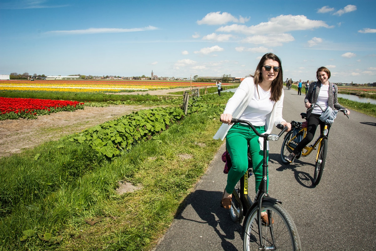 Two girld biking through tulips in the Netherlands
