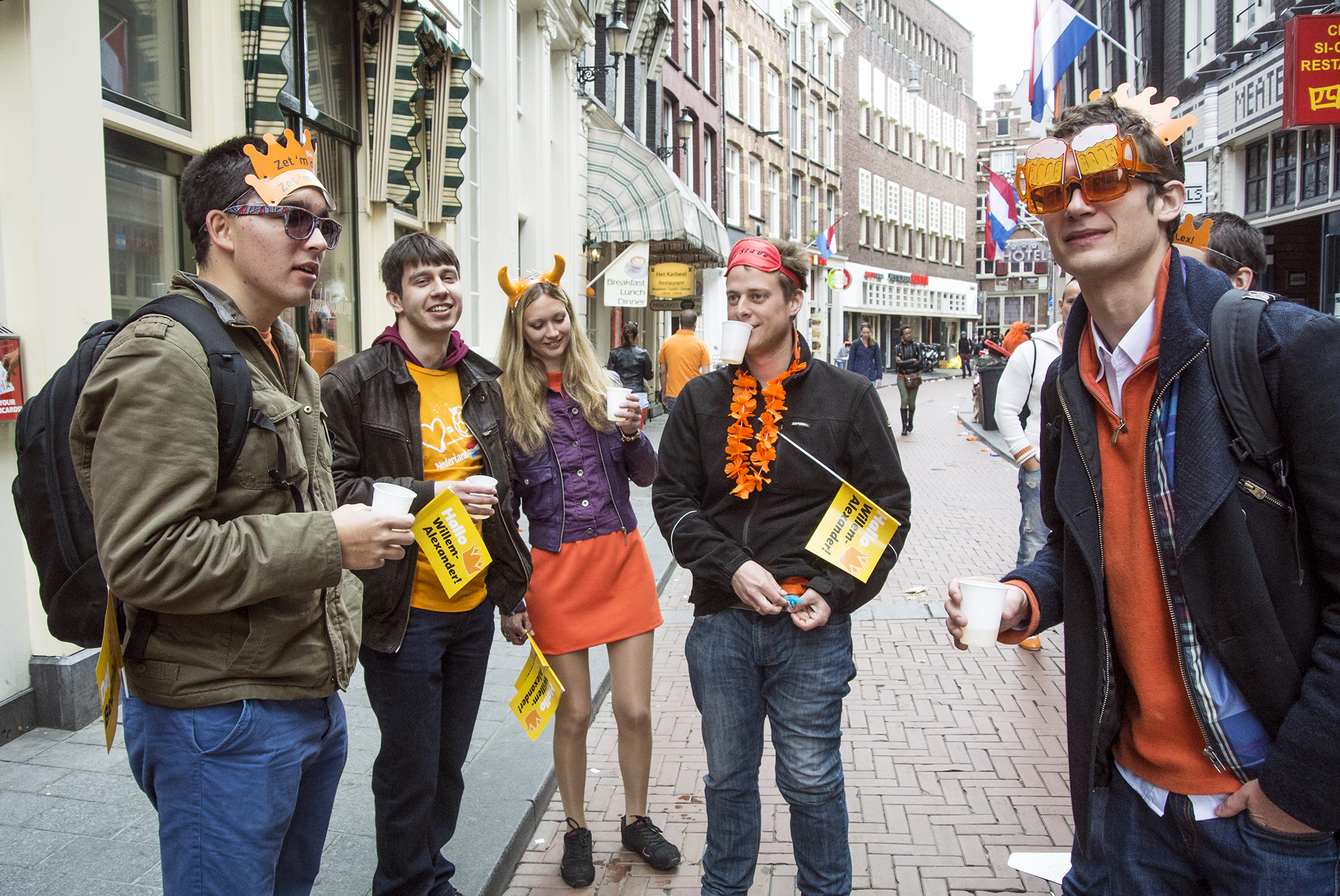 Several people drinking on the street while being dressed up for King's Day