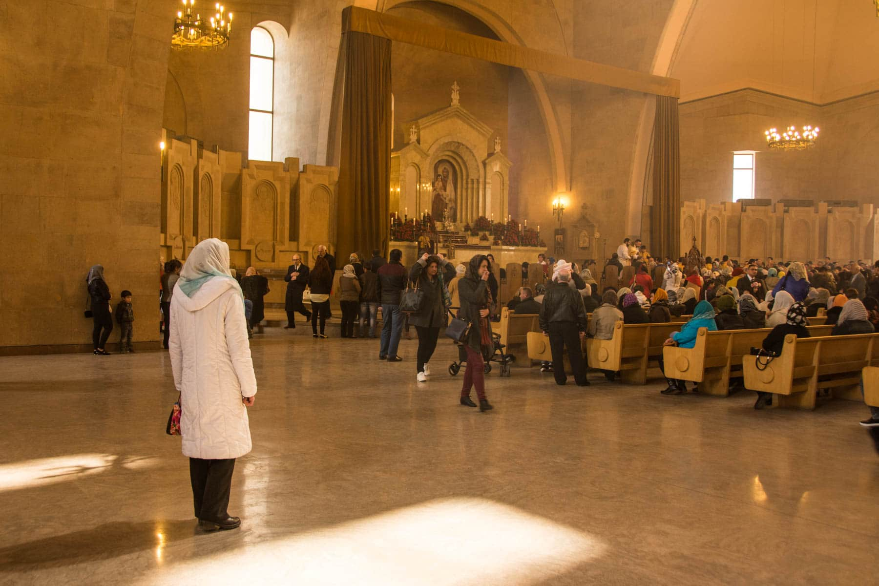 Easter in Armenia - A woman standing and observing mass in Gregory the Illuminator Cathedral in Yerevan for Easter in Armenia