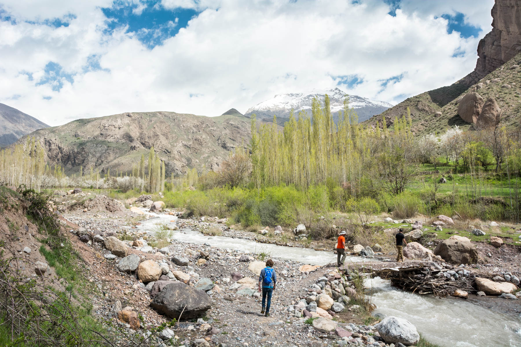 Two men crossing a stream to enter gorges in the Alamut Valley in Iran