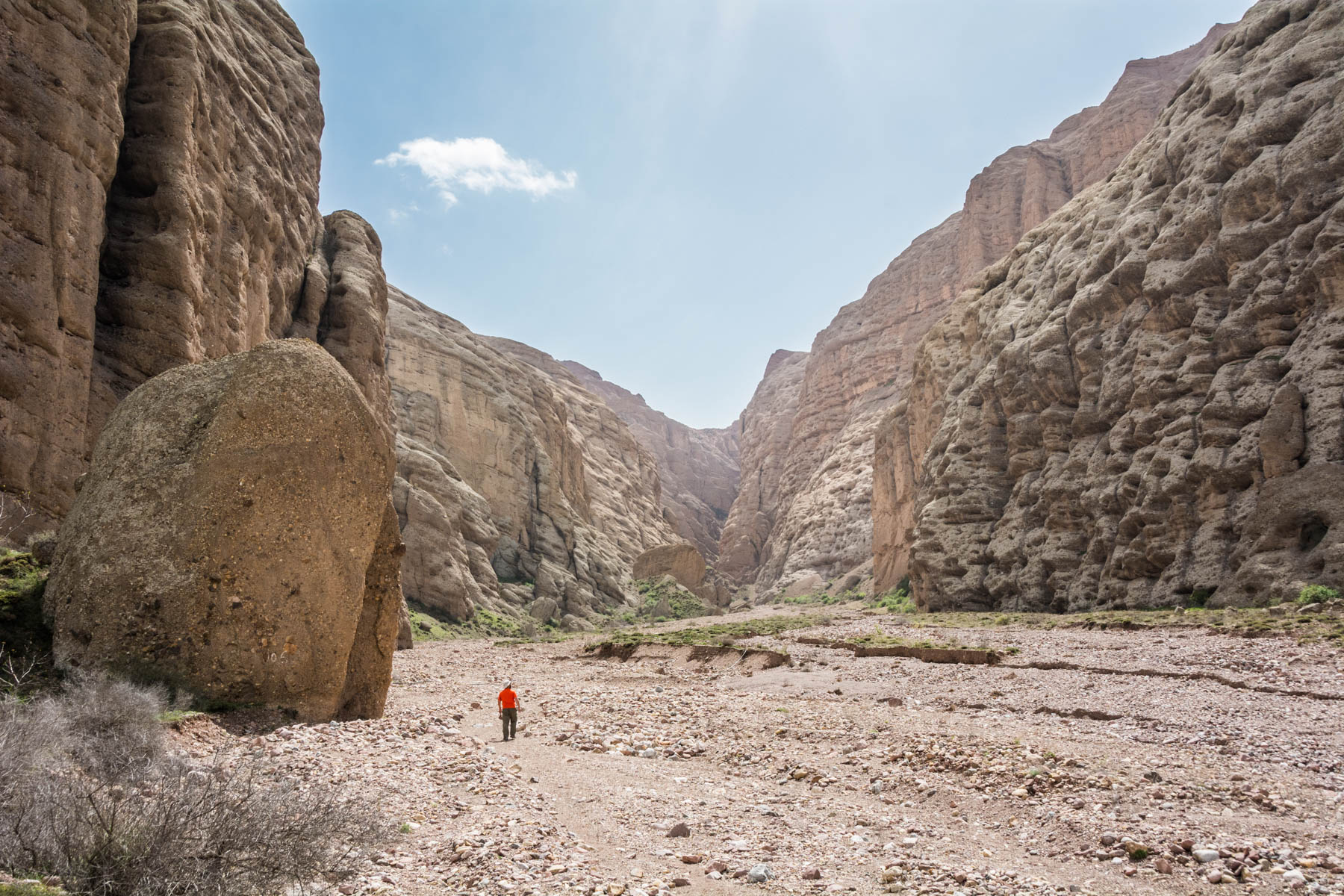 A man walking through the red rock gorges of the Alamut Valley in Iran.