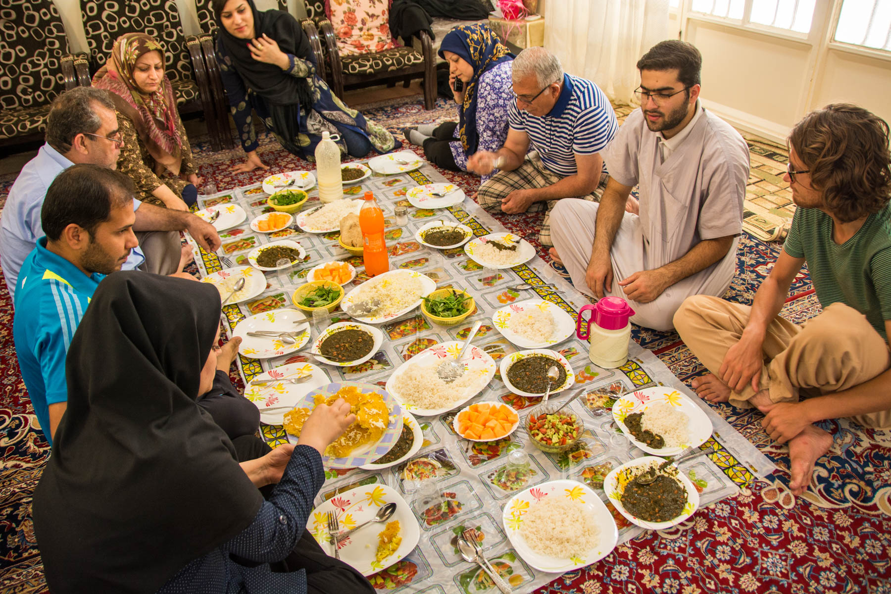 People sitting down for a traditional Iranian dinner