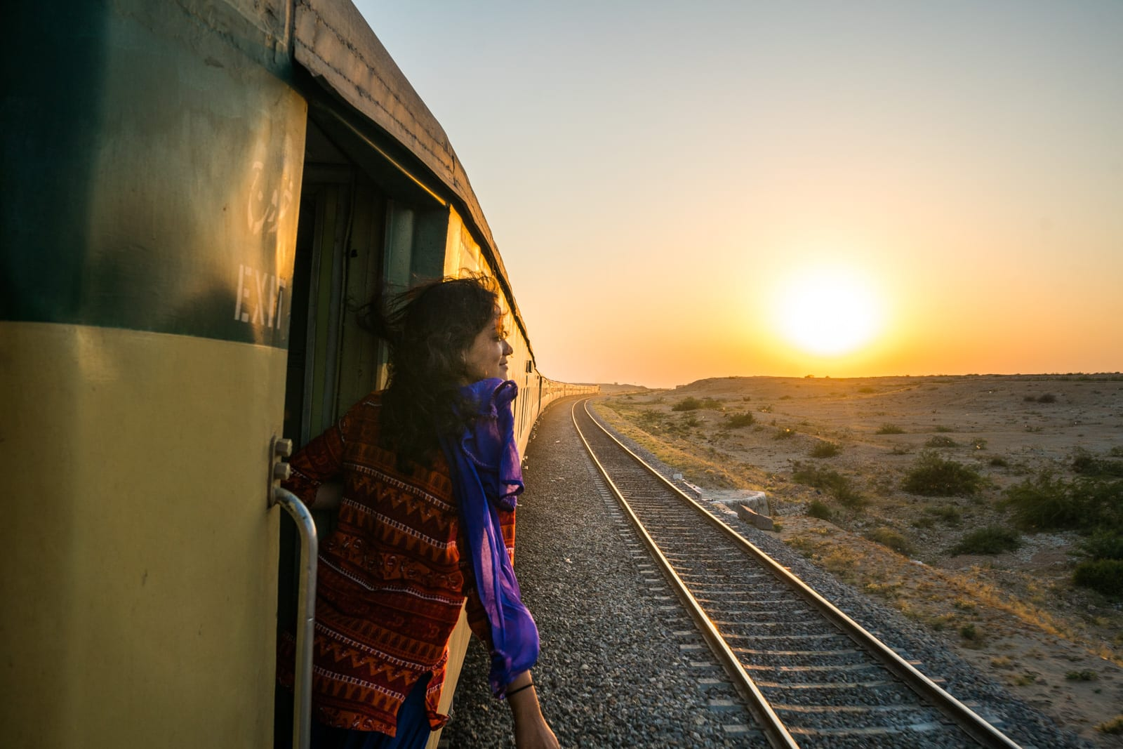 A girl hanging out the door of a moving train in Pakistan