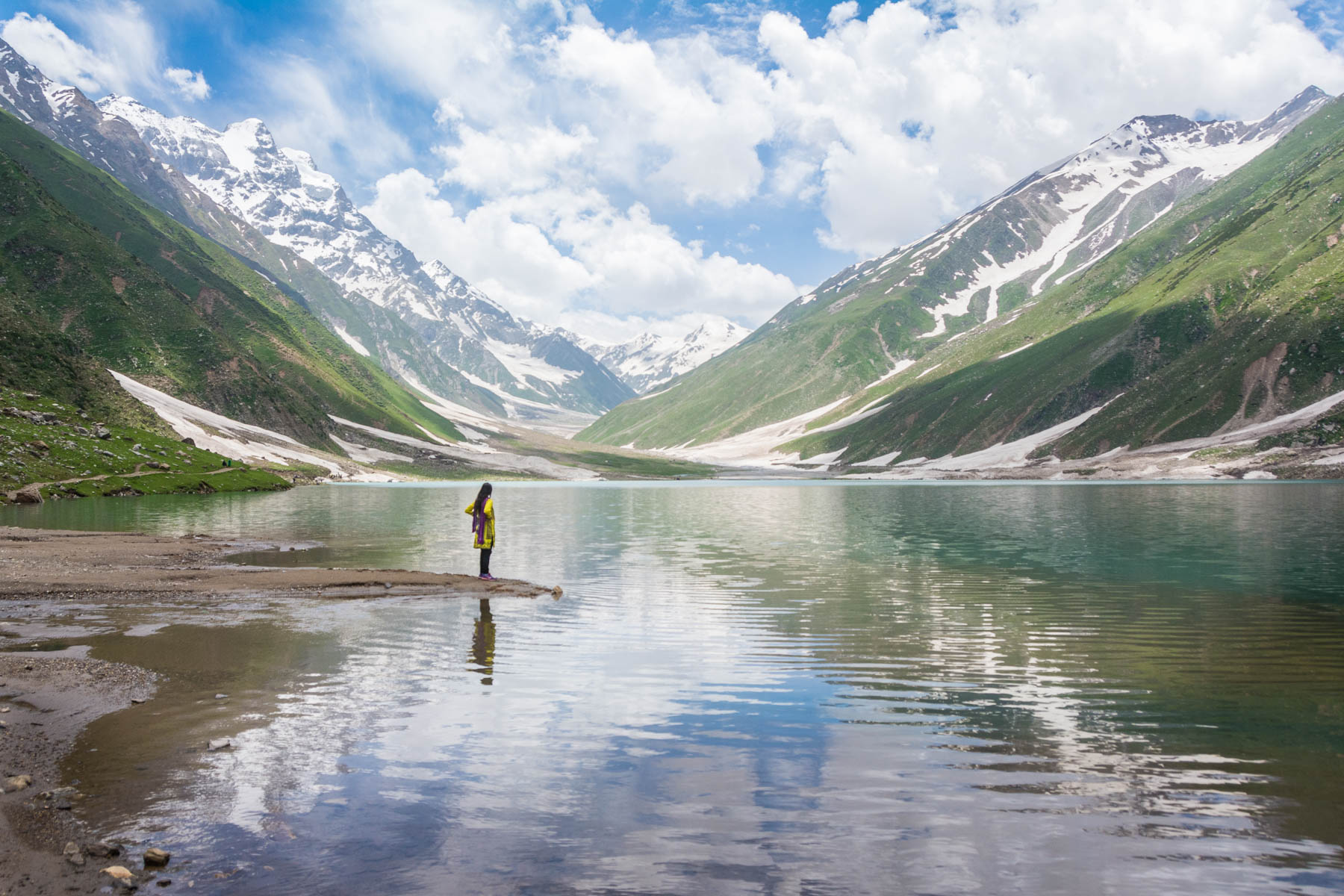 A solo female traveler standing near a lake in Pakistan