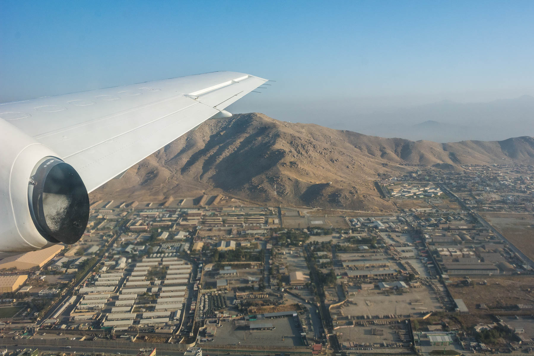 A plane flying over Kabul with views of the city