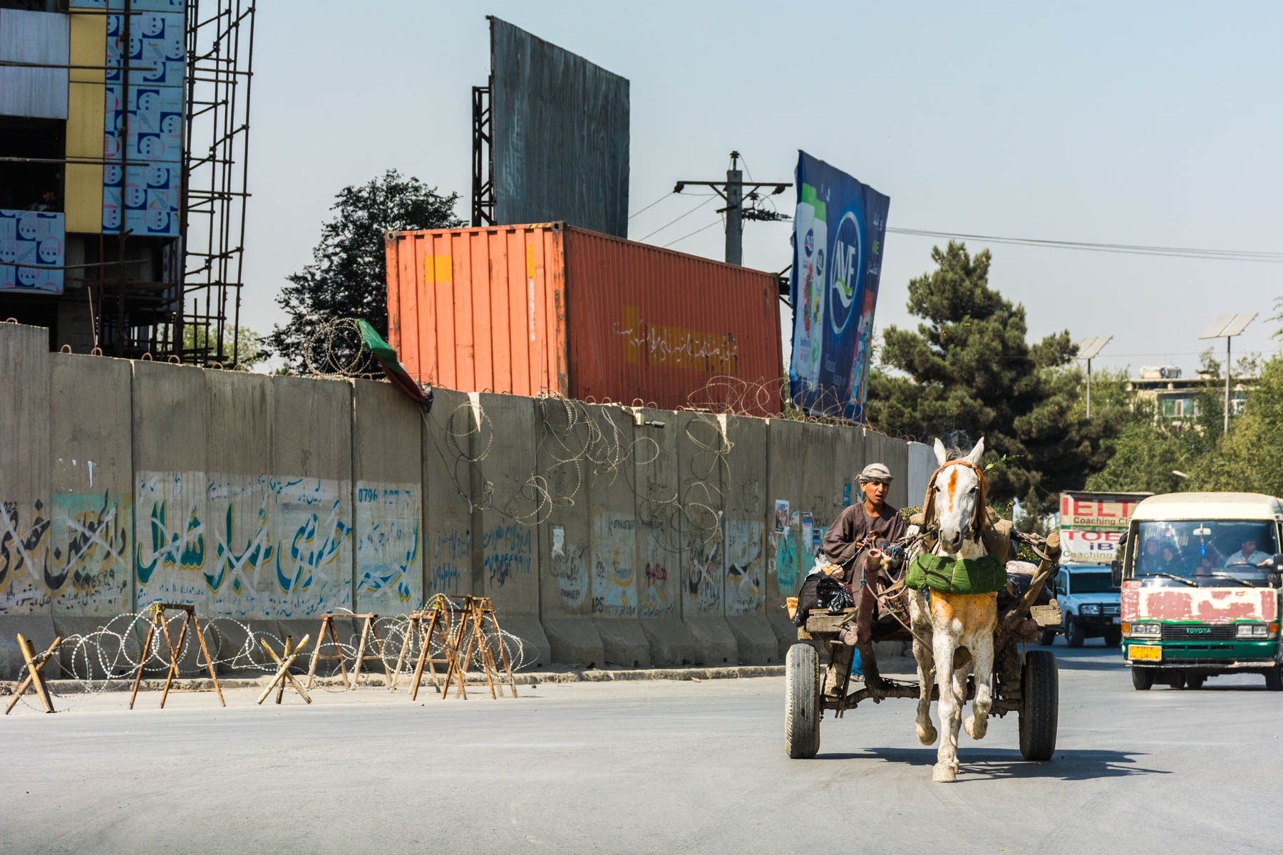 A donkey cart passing a blast wall in Kabul, Afghanistan