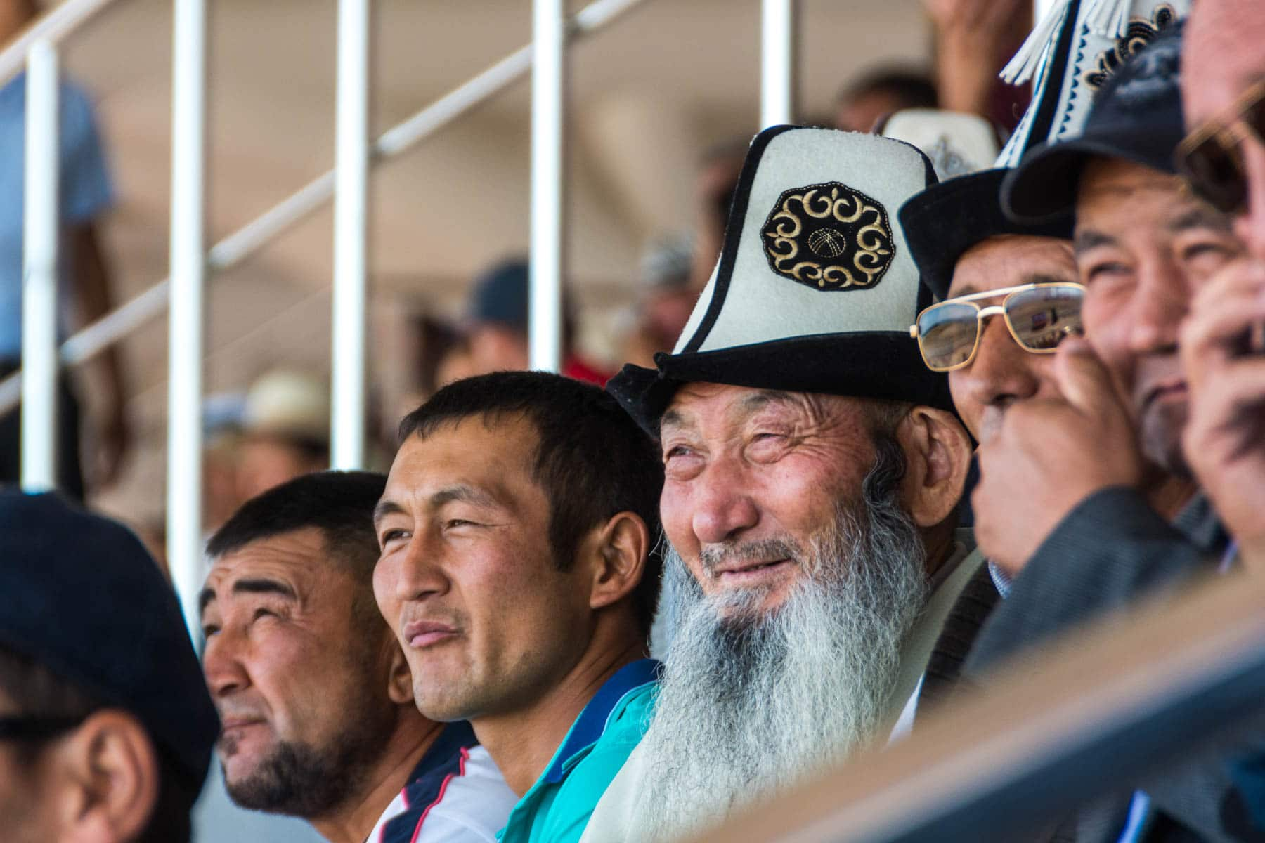 A bossy old Kyrgyz man wearing a traditional hat