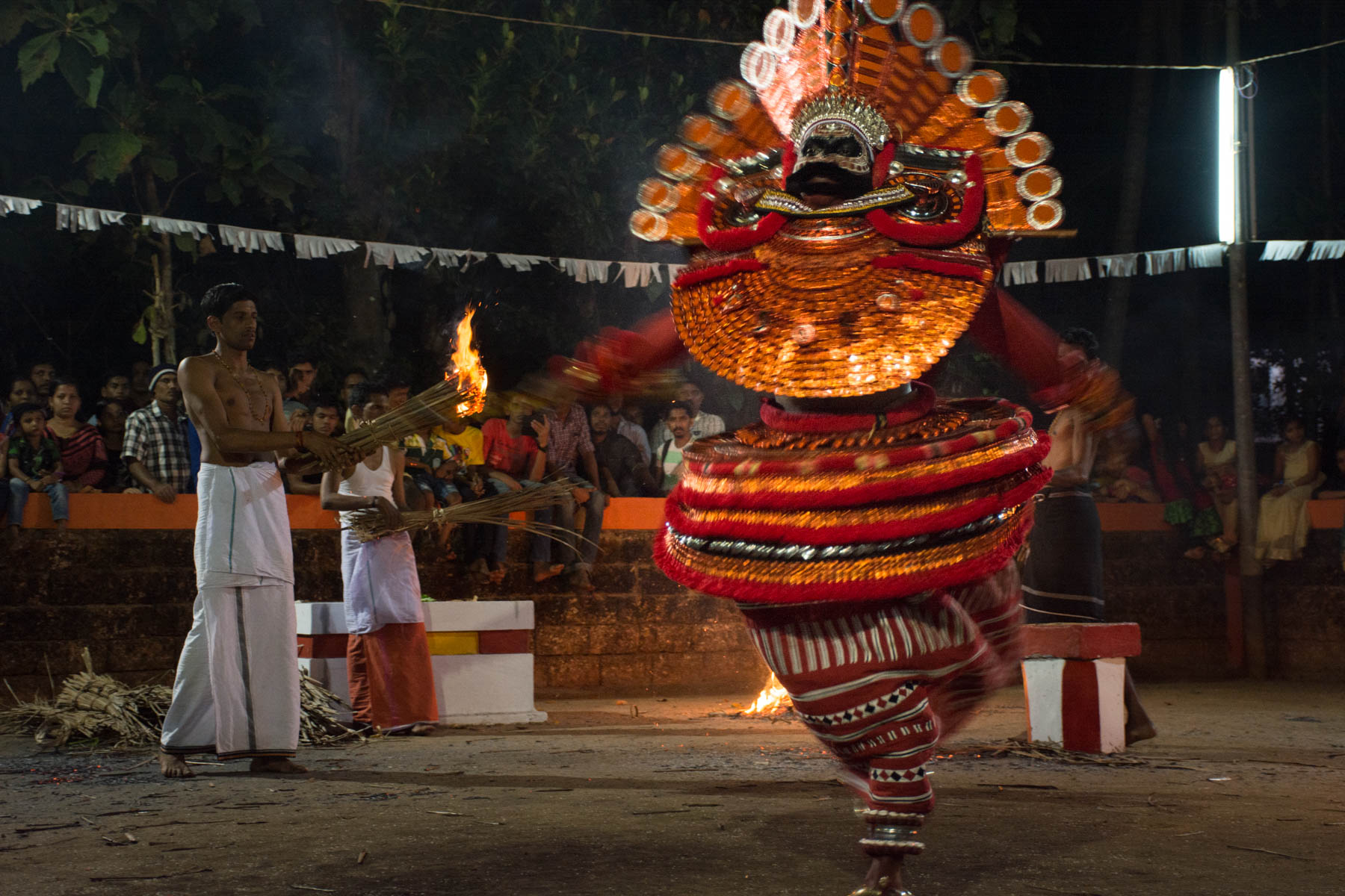 Spinning Theyyam dancer with a priest in the background