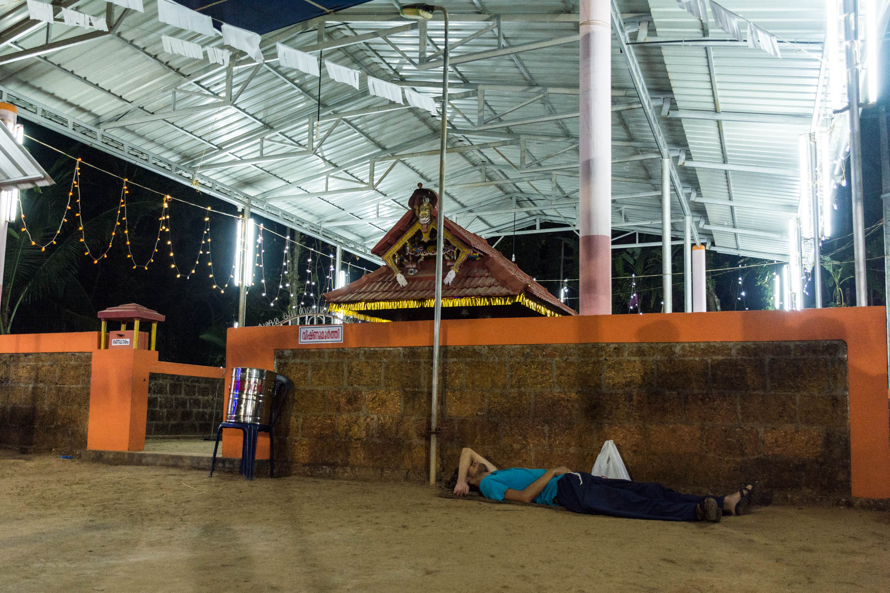 Boy sleeping on the floor at a temple after the performance