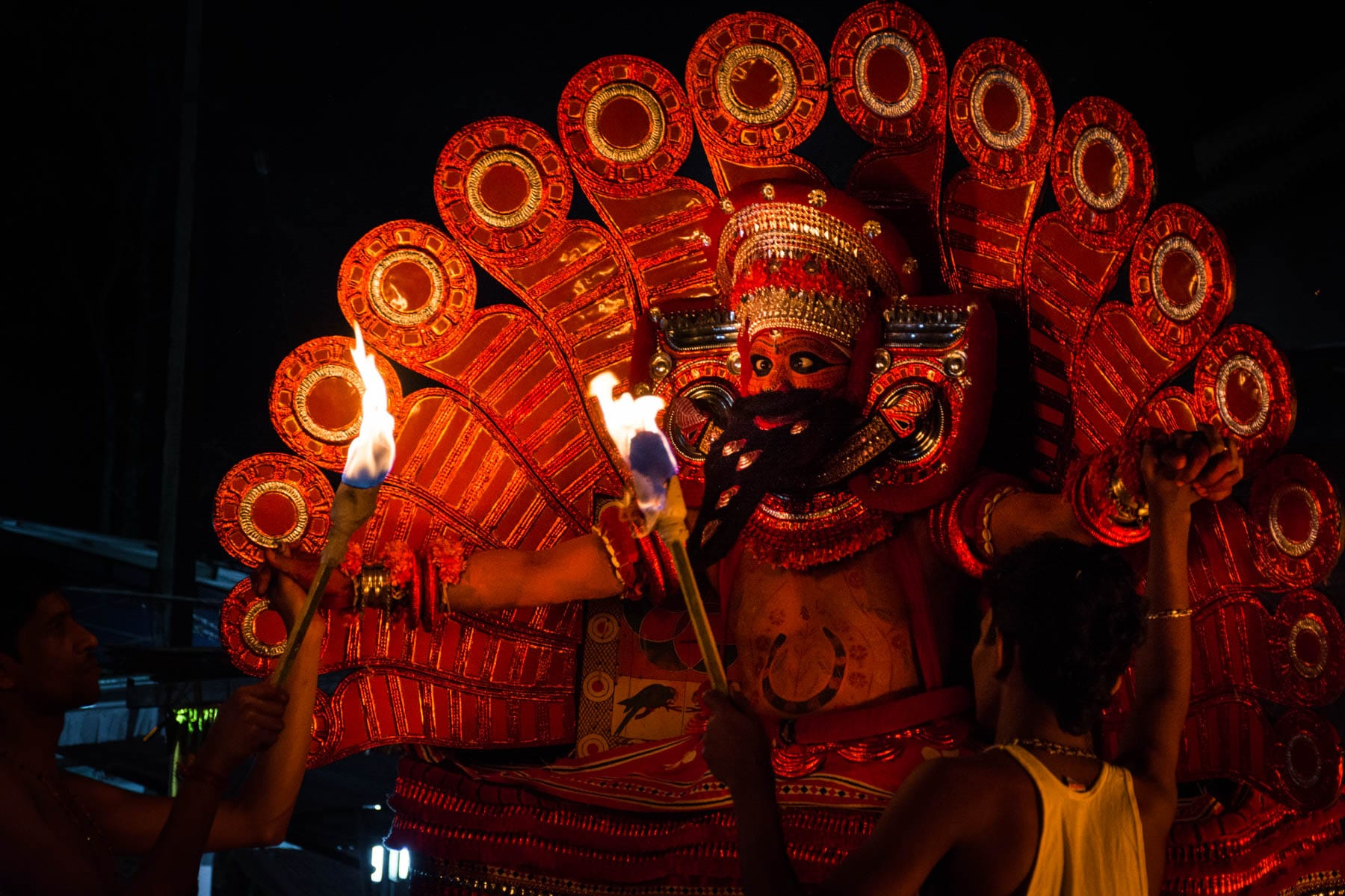 Kutty being supported by priests hands - Where to see Theyyam in Kerala, India - Lost With Purpose