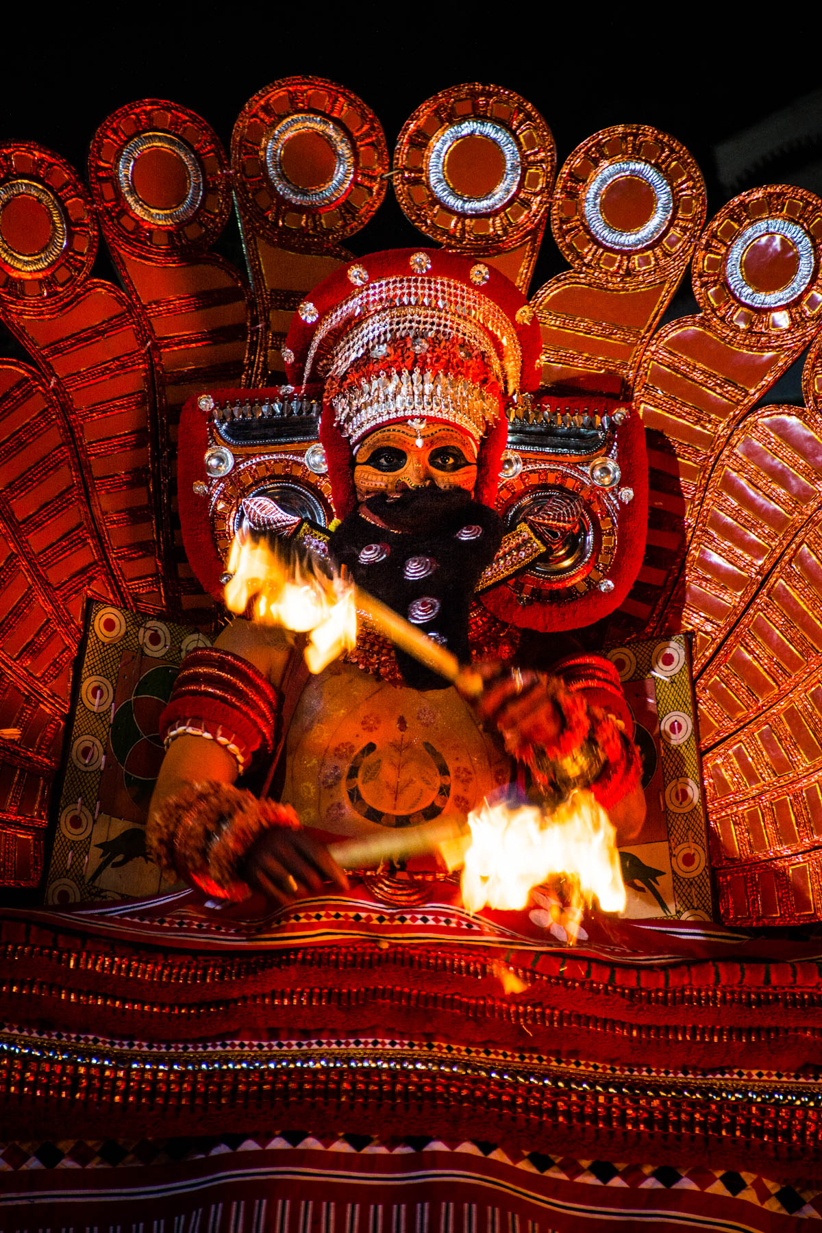 A close up shot of the Kutty Theyyam peformer playing with fire