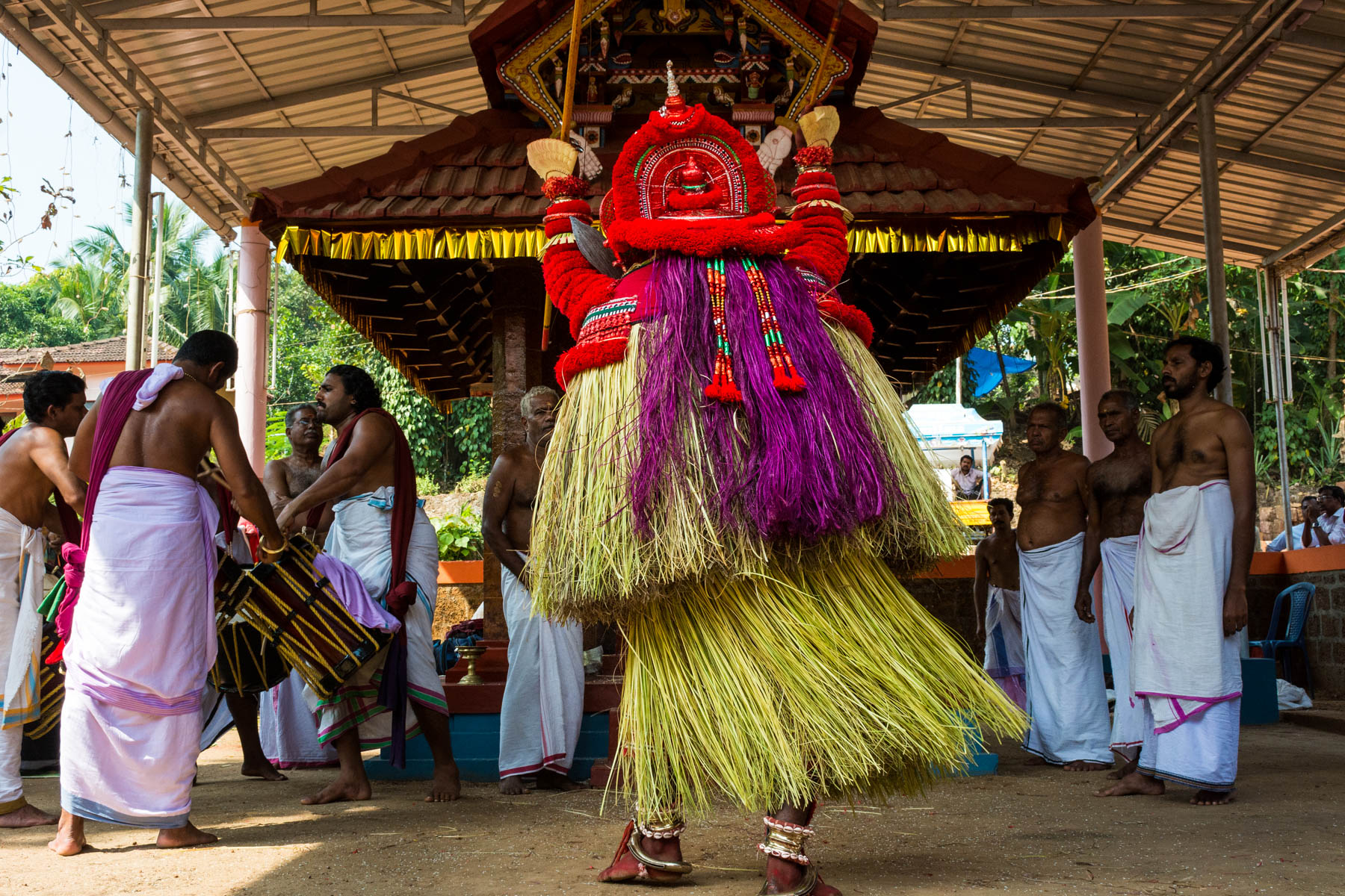 A performer doing a Theyyam dance before a shrine