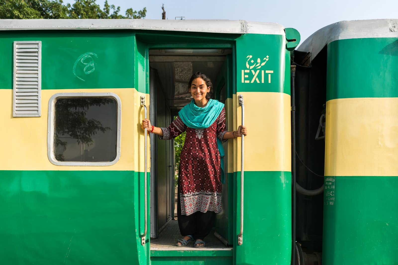 A girl hanging out of an open train door in Pakistan