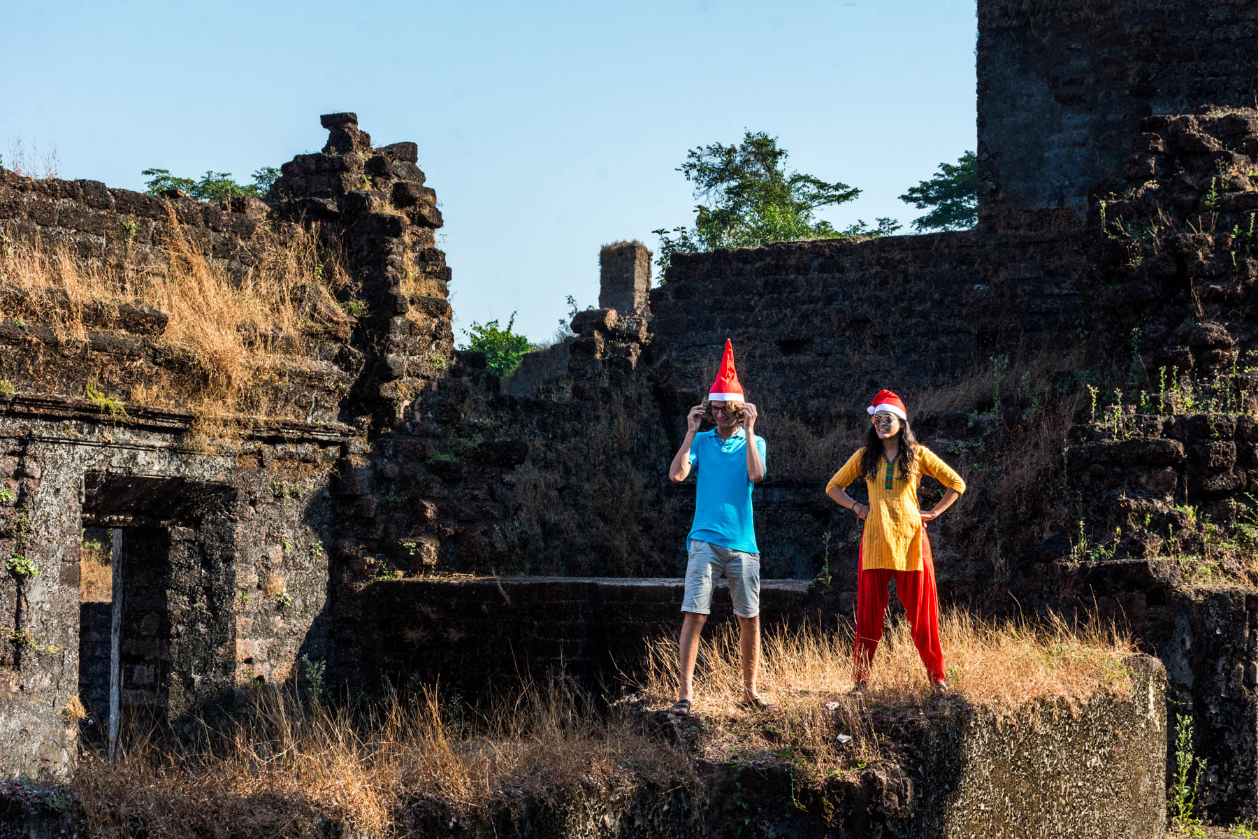 Two foreigners wearing Santa hats in church ruins