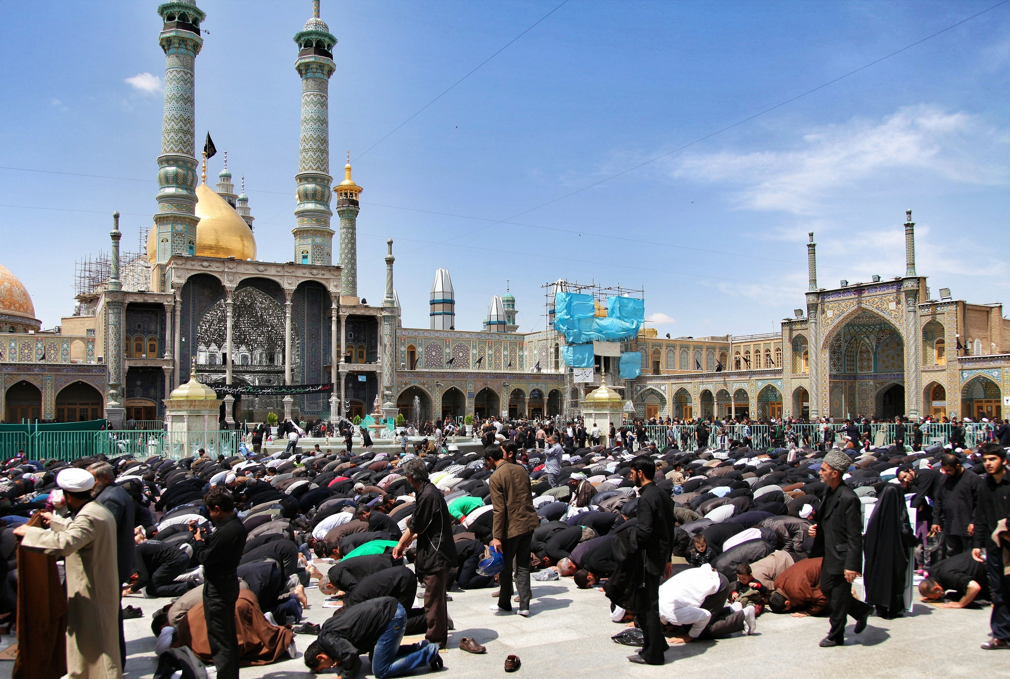 Two week Iran travel itinerary - Men praying at Hazrat-e Masumeh shrine in Qom, Iran - Lost With Purpose
