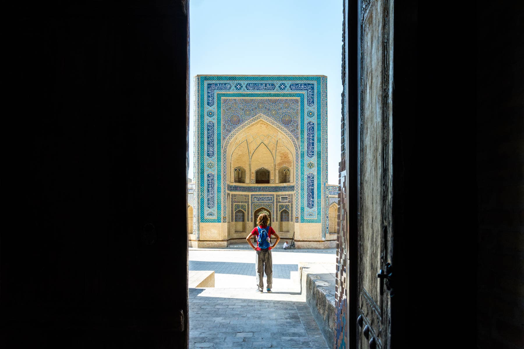 A boy Looking through doors to the Kaylan mosque in Bukhara
