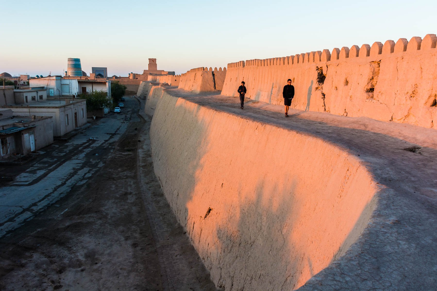 Boy walking on the walls of Khiva's old city during sunrise