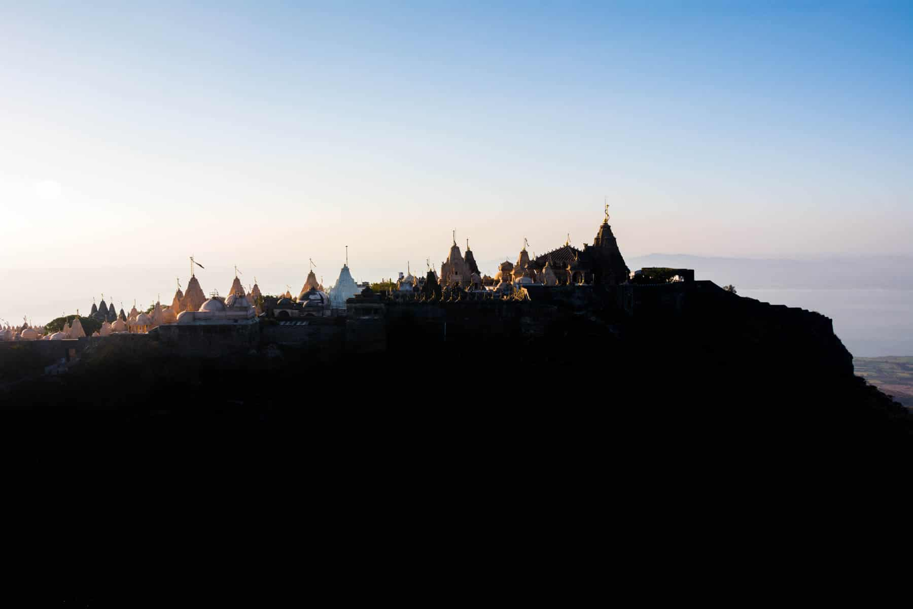 A Jain pilgrimage in Palitana, India - The holy mountain of Girnar with silhouettes of the temples near Palitana - Lost With Purpose
