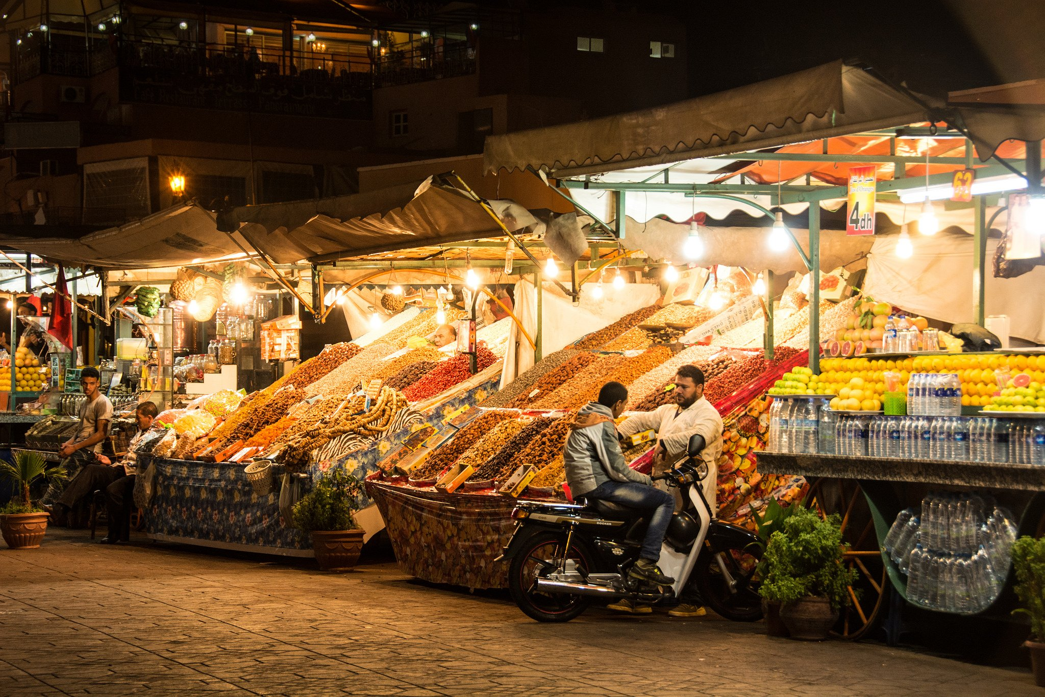 What is baksheesh and where is it found? - Men standing in the Jeema el-Fnaa bazaar at night in Marrakesh, Morocco - Lost With Purpose