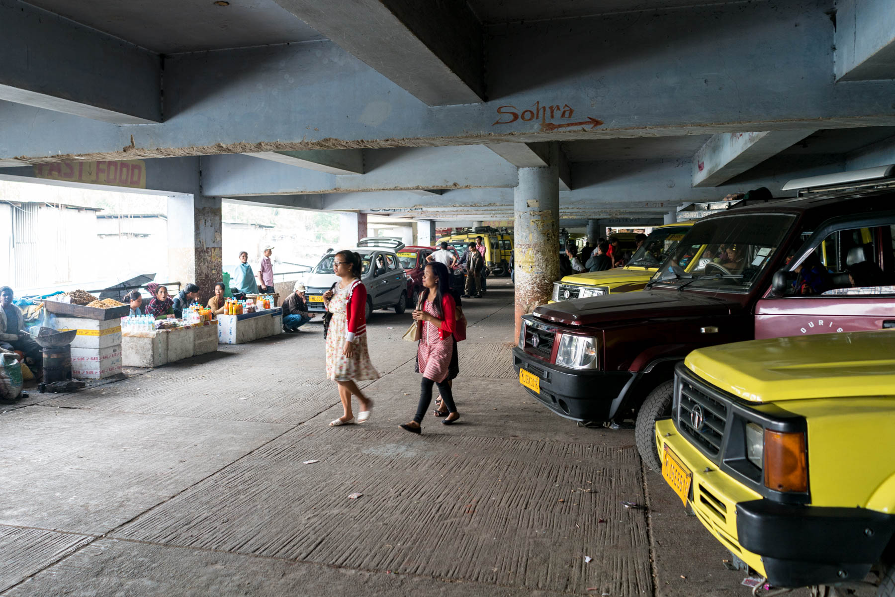 Girl walking in the shared Sumo stand in a parking garage in Shillong