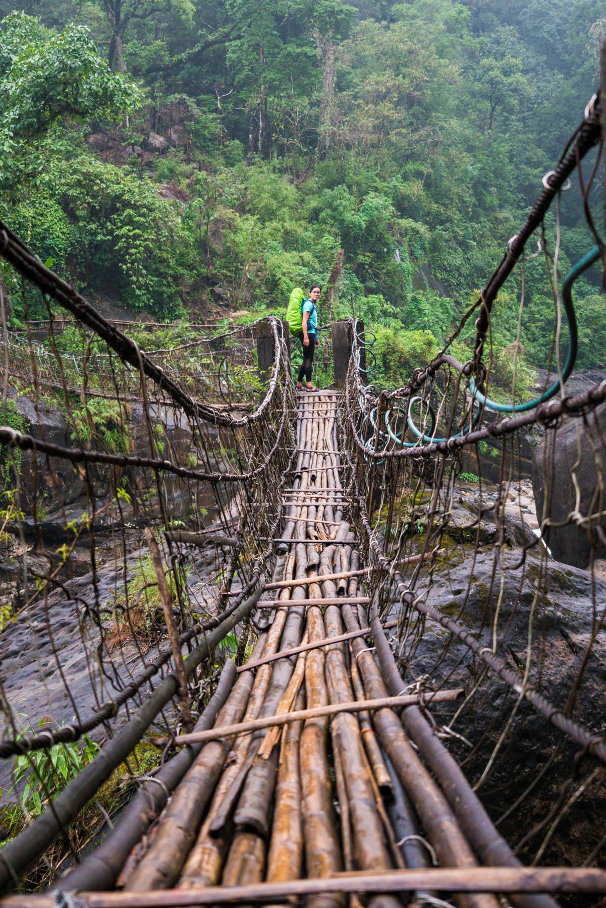 Photo essay of Nongriat and the living root bridges of Meghalaya, India - Alex standing at the end of a suspension bridge - Lost With Purpose