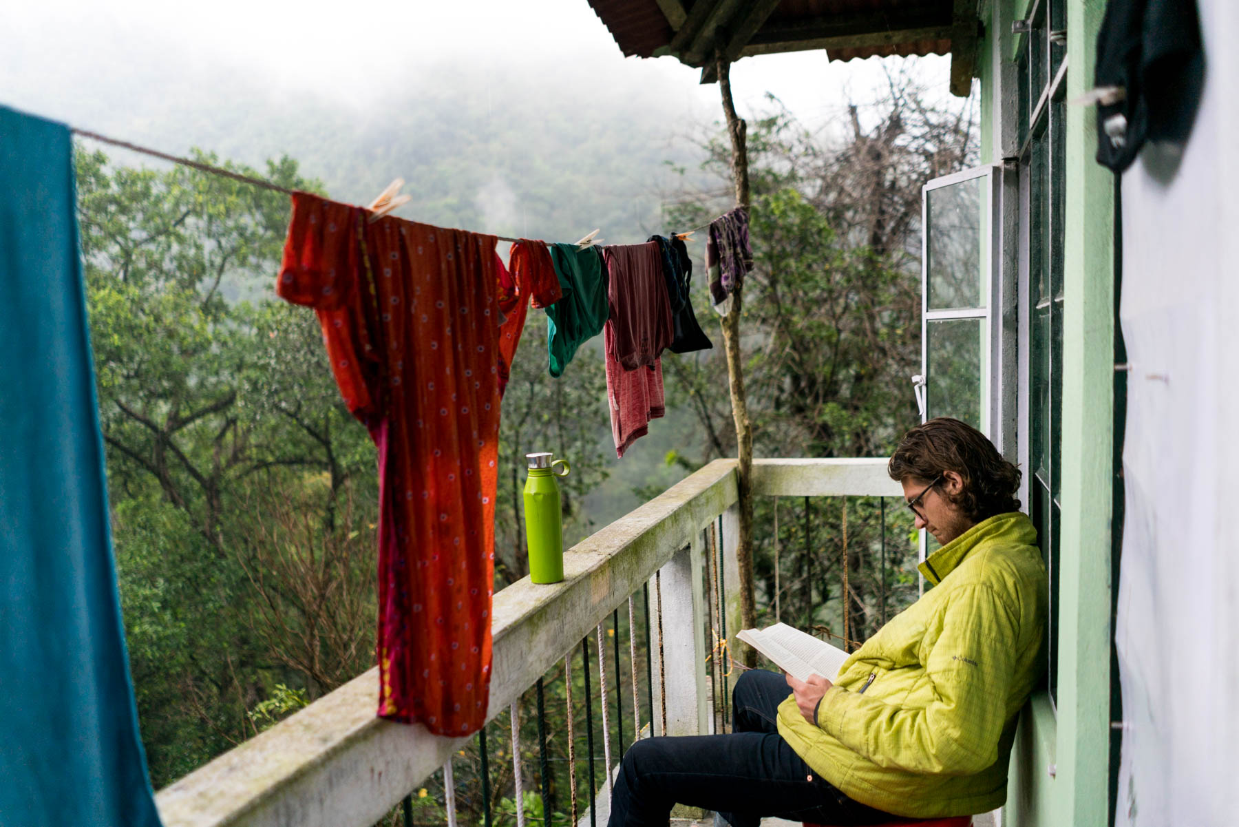 Photo essay of Nongriat and the living root bridges of Meghalaya, India - Sebastiaan reading in the rain - Lost With Purpose