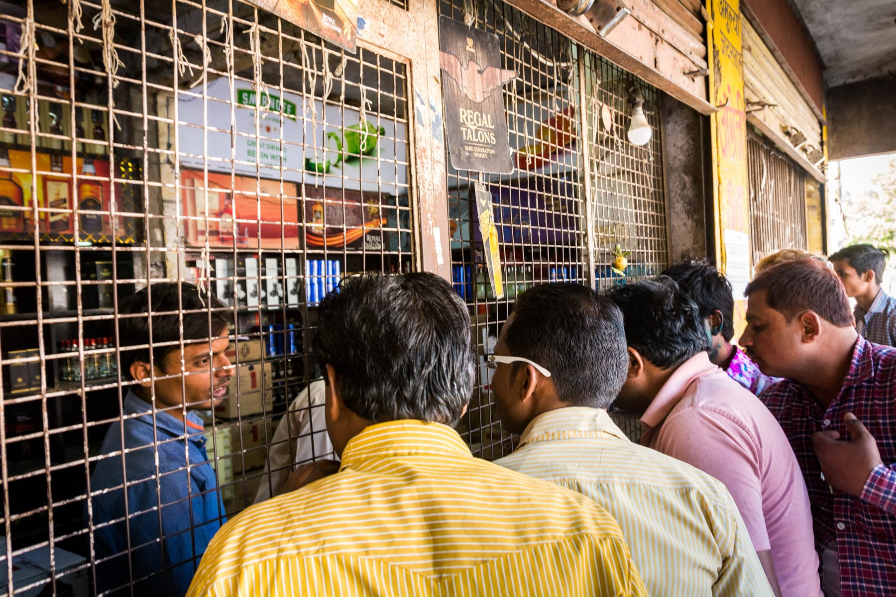 What you need know about playing Holi in Varanasi, India - Crowd at the wine shop in Varanasi before Holi - Lost With Purpose