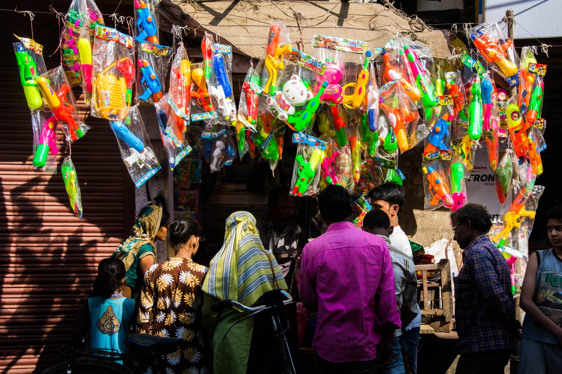 What you need know about playing Holi in Varanasi, India - Locals buying water guns in preparation for Holi in Varanasi - Lost With Purpose