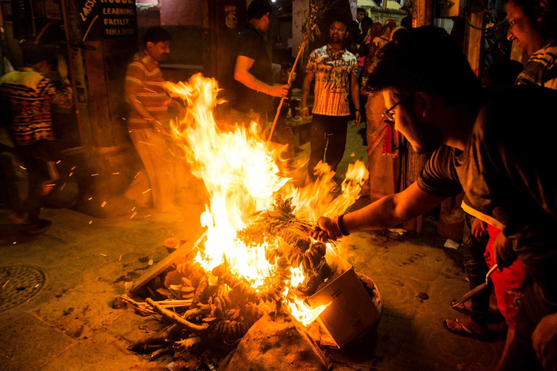 What you need know about playing Holi in Varanasi, India - People putting offerings into the fire on Holika Dahan, the night before Holi - Lost With Purpose