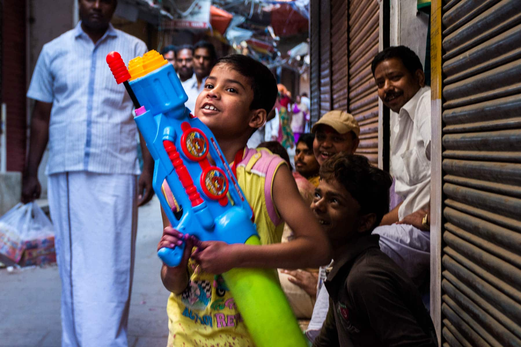 What you need know about playing Holi in Varanasi, India - A young boy with a large water gun - Lost With Purpose