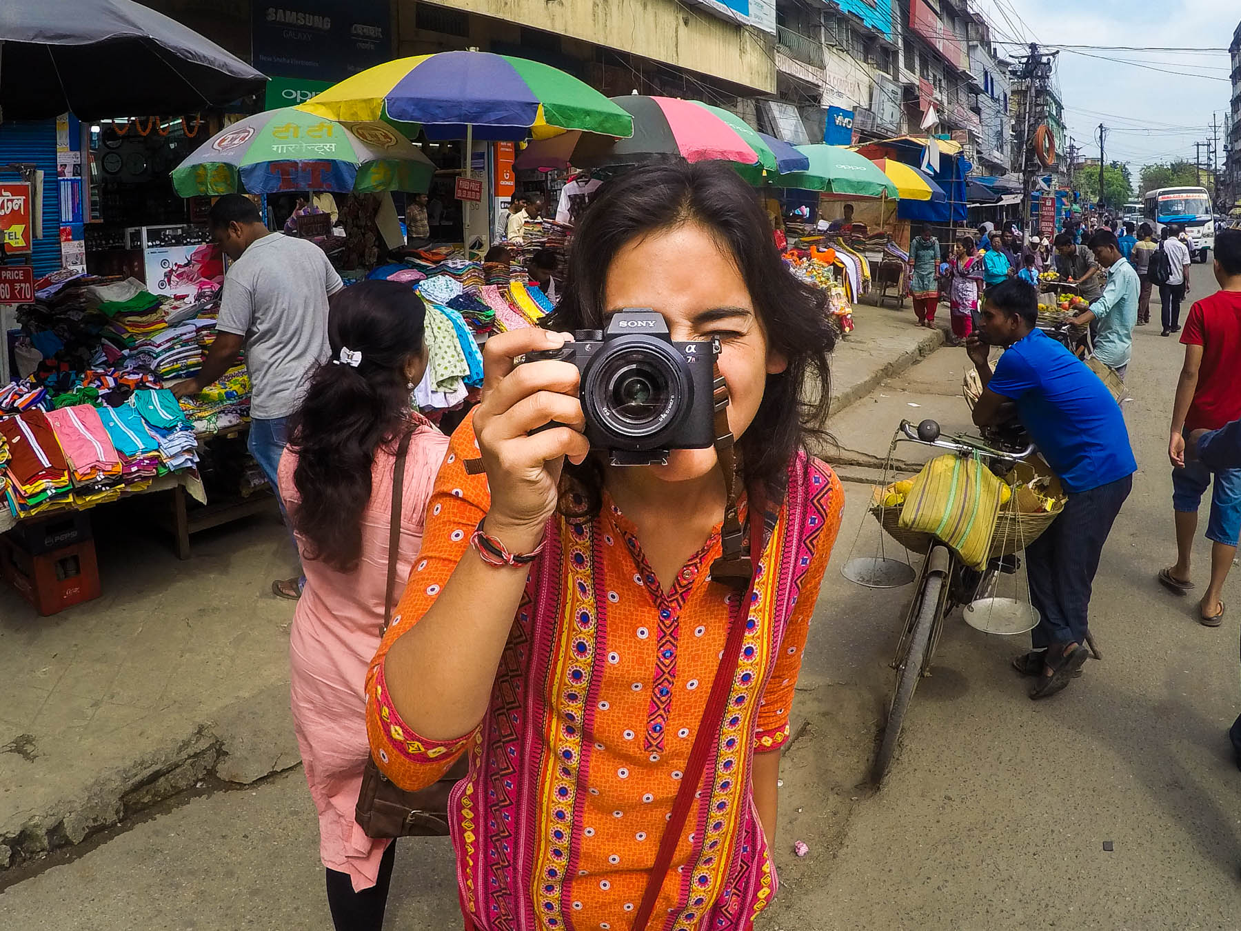 How to upgrade from a Nikon DSLR to a Sony a7RII mirrorless full-frame camera, the best travel camera out there - Alex with a Sony a7RII in a market in Assam, India - Lost With Purpose