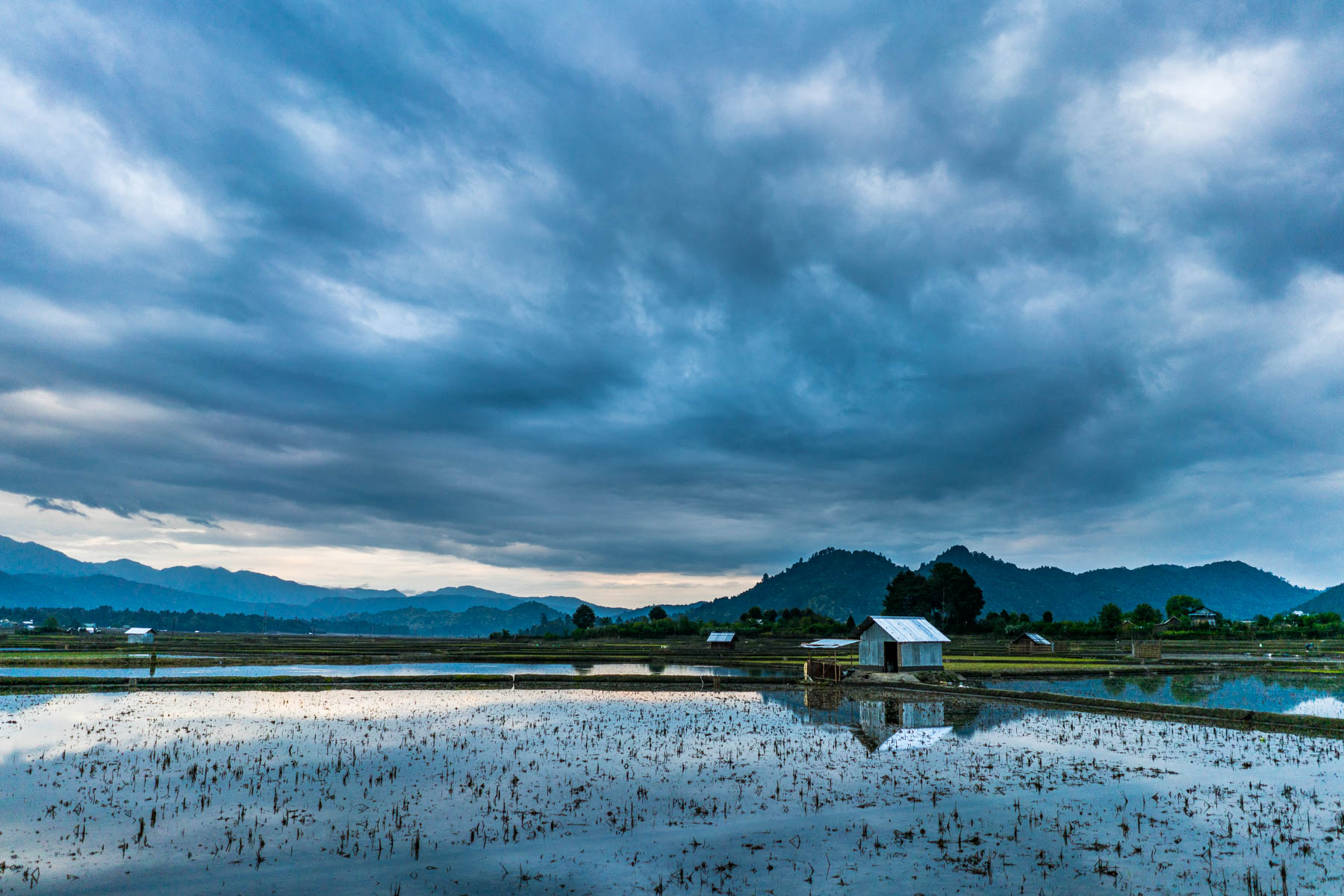 Backpacking in Arunachal Pradesh travel guide - Epic clouds reflecting over rice paddy waters in Ziro Valley - Lost With Purpose