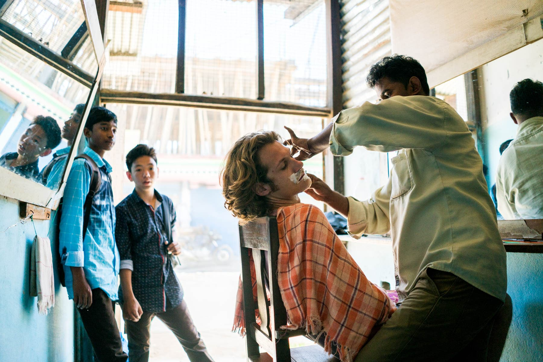 Backpacking in Arunachal Pradesh, India - Sebastiaan getting a cheap shave in Daporijo - Lost With Purpose