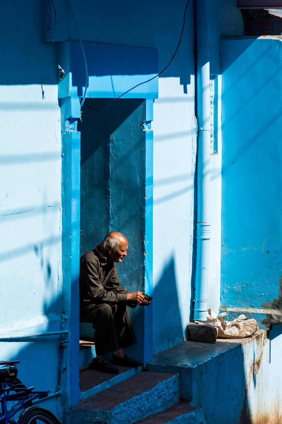 Photo essay about the streets and people of the Blue City of Jodhpur, Rajasthan, India - A man sitting on a blue stoop - Lost With Purpose