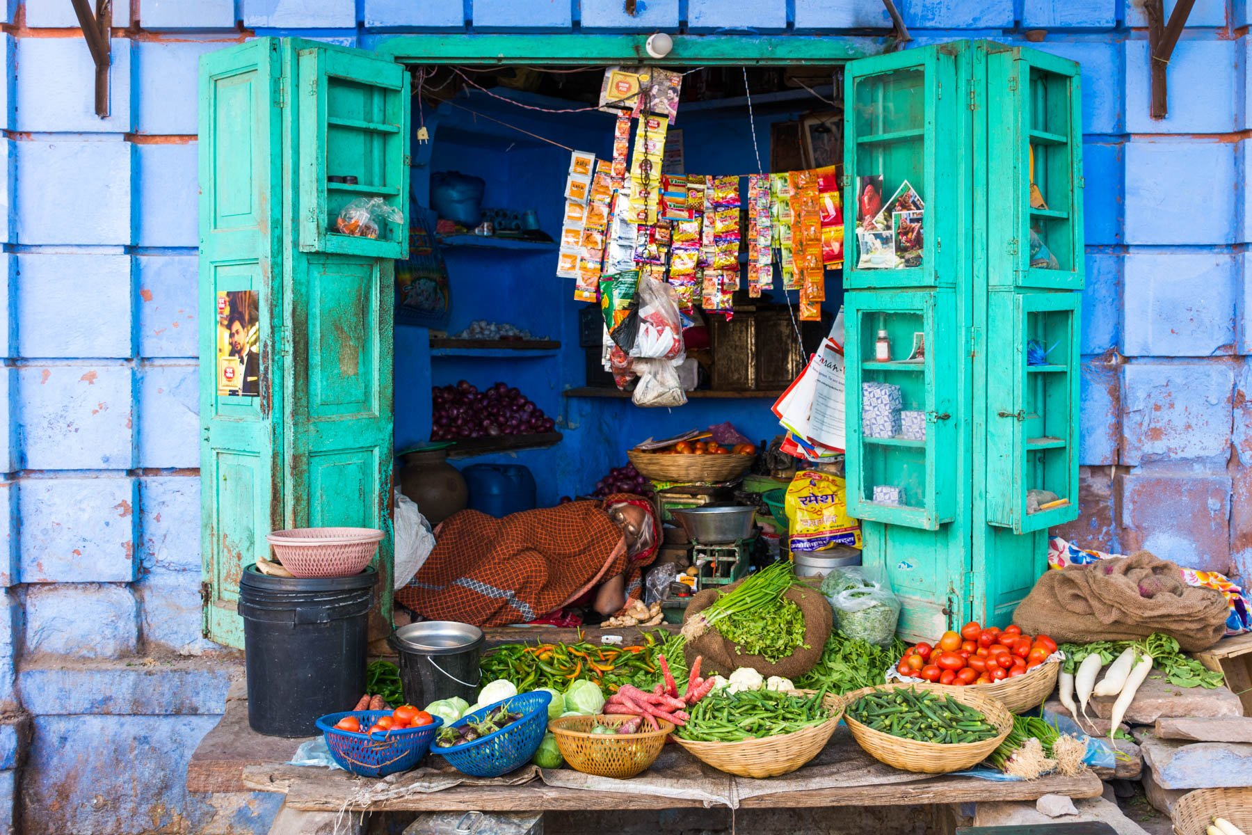 Photo essay about the streets and people of the Blue City of Jodhpur, Rajasthan, India - Sleeping aunty storekeeper in a blue storefront - Lost With Purpose