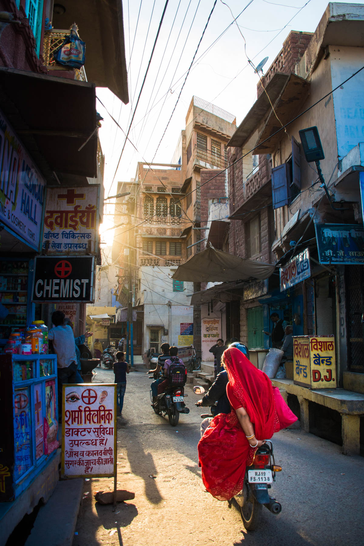 A lady in a red sari zipping past on a motorbike during sunset in Jodhpur, Rajasthan, India.