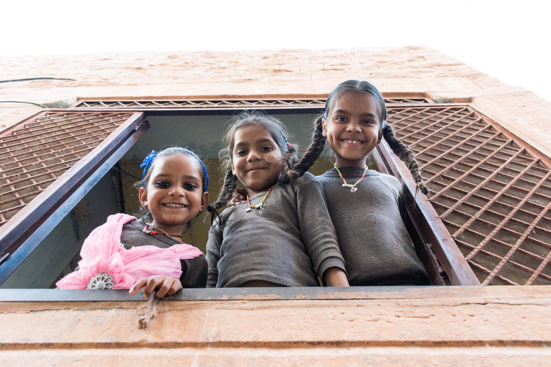 Girls hanging out the window in Jodhpur