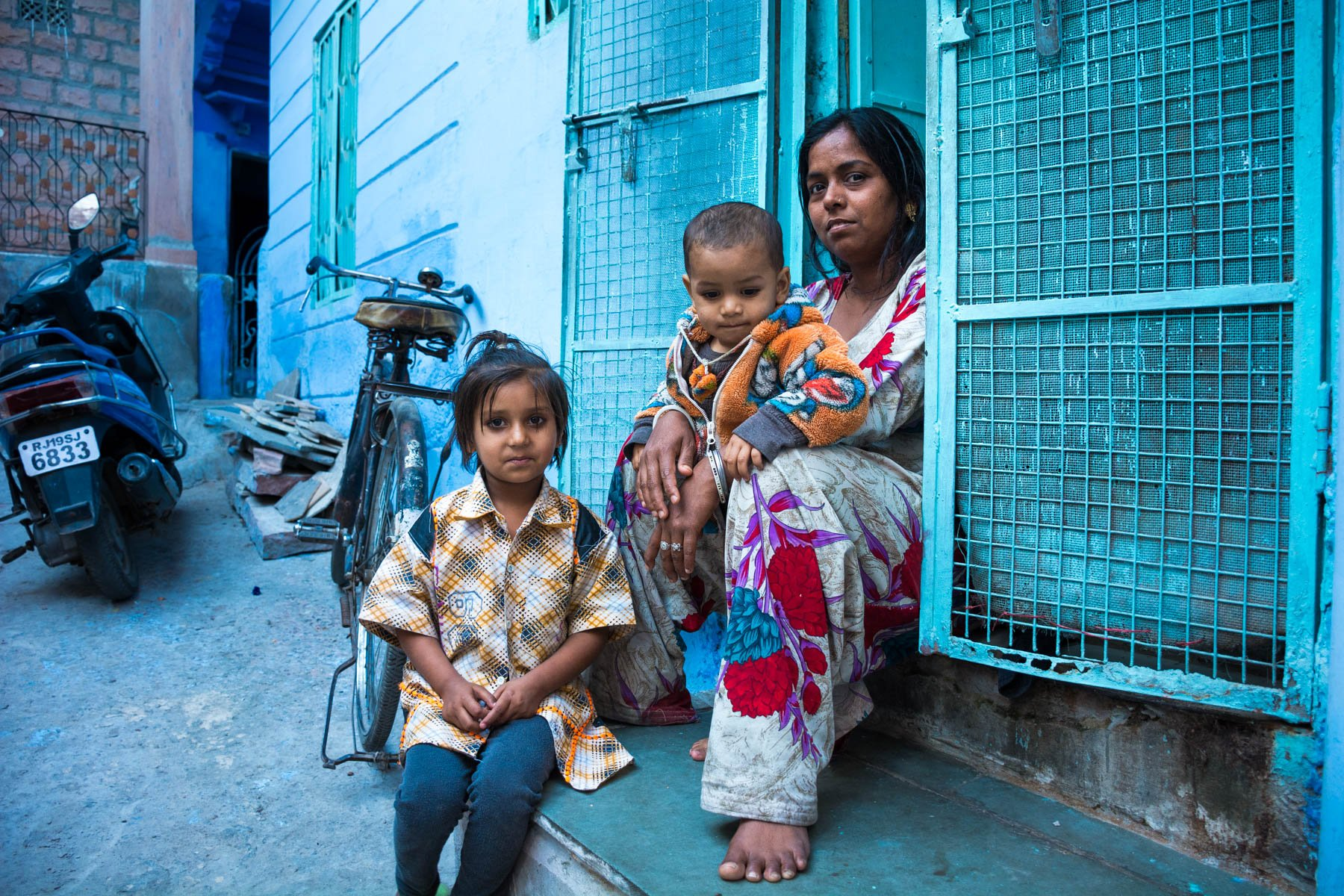 Photo essay about the streets and people of the Blue City of Jodhpur, Rajasthan, India - A local woman in front of a house in Jodhpur - Lost With Purpose