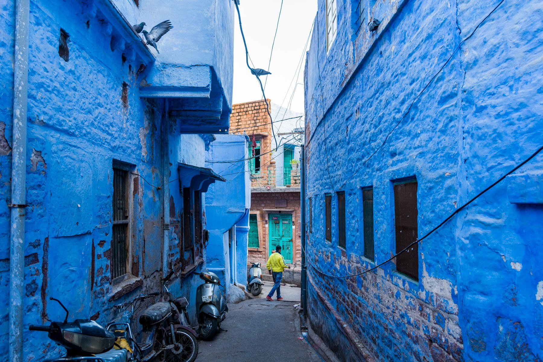 A man walking through a blue neighborhood in Jodhpur