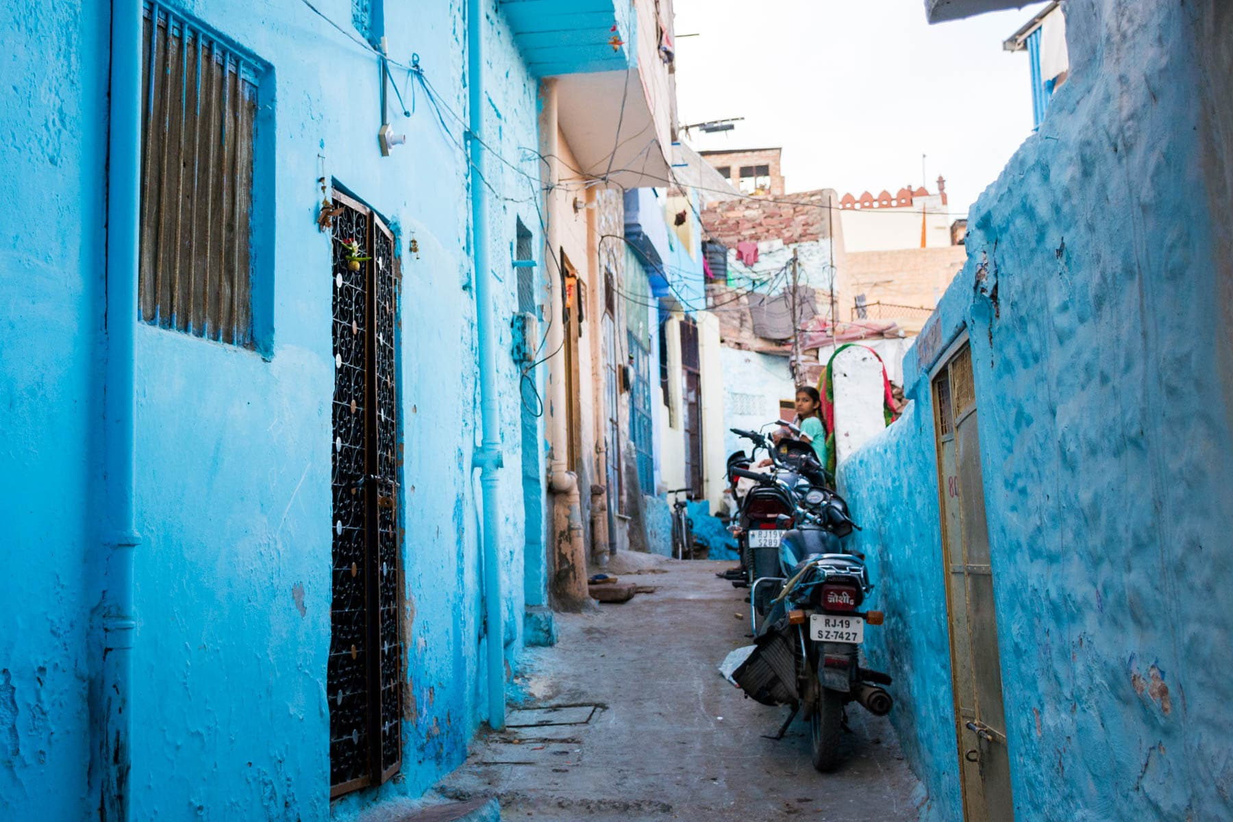 Photo essay about the streets and people of the Blue City of Jodhpur, Rajasthan, India - A girl in a blue neighborhood - Lost With Purpose