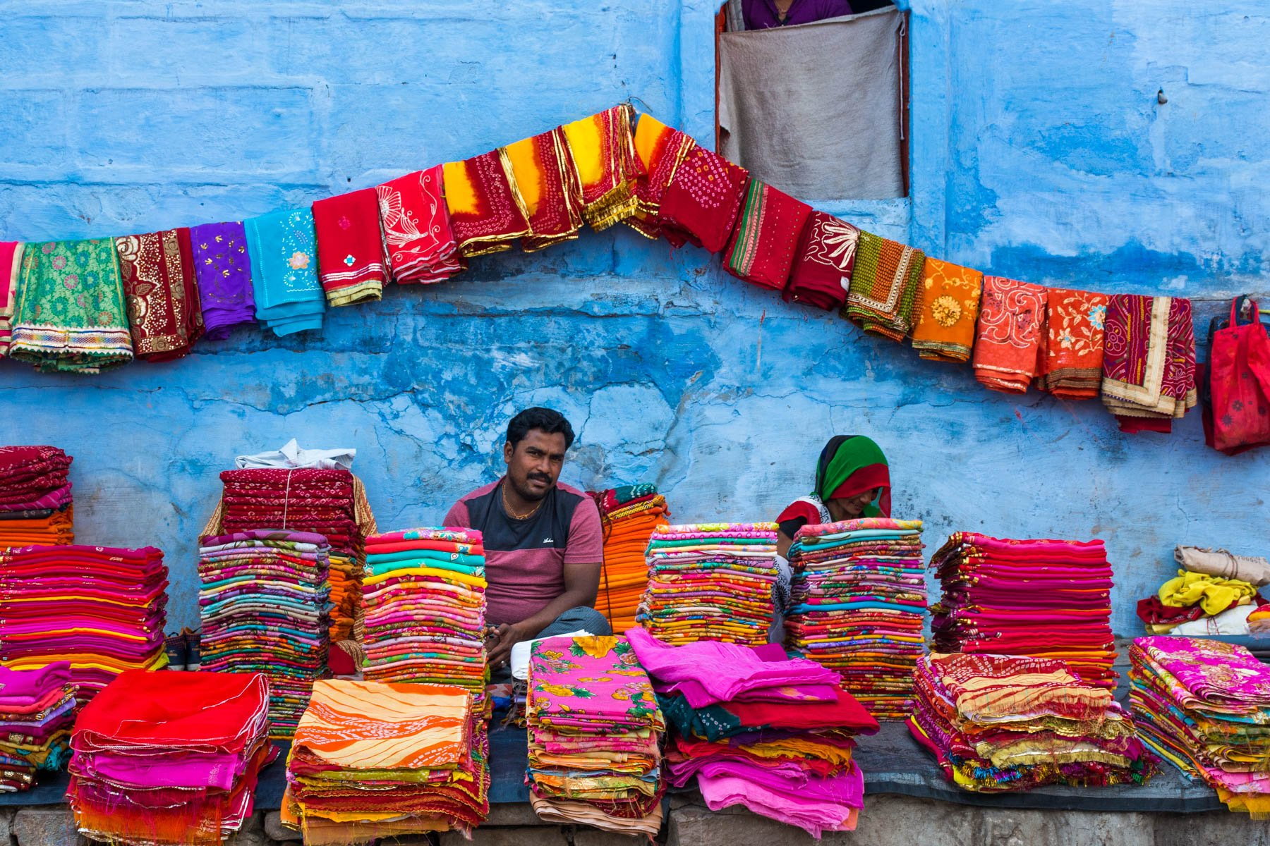 A man selling fabric in front of a blue building