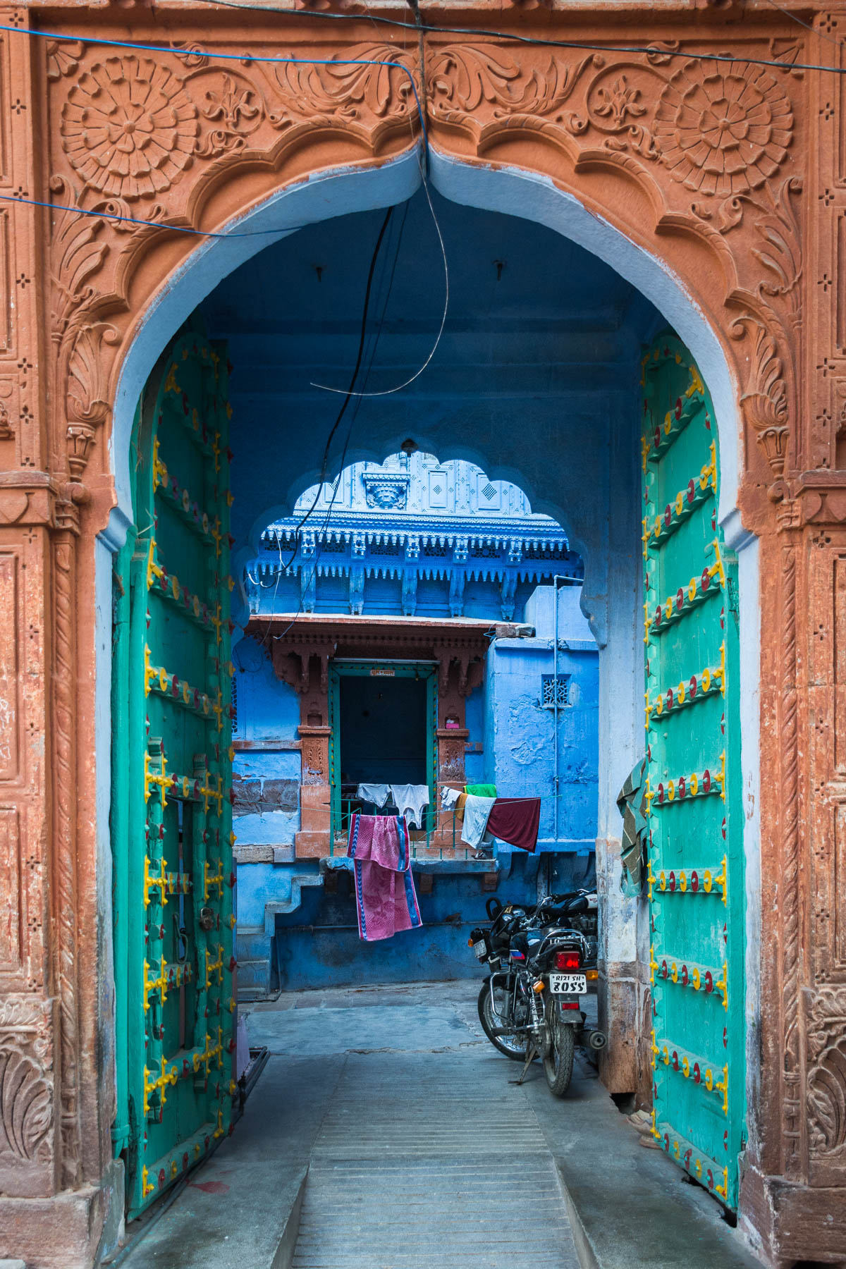 A blue house and beautifully detailed archway and door in Jodhpur, Rajasthan, India