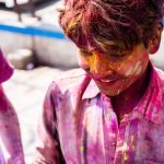 What you need know about playing Holi in Varanasi, India - A local boy covered with pink colors - Lost With Purpose
