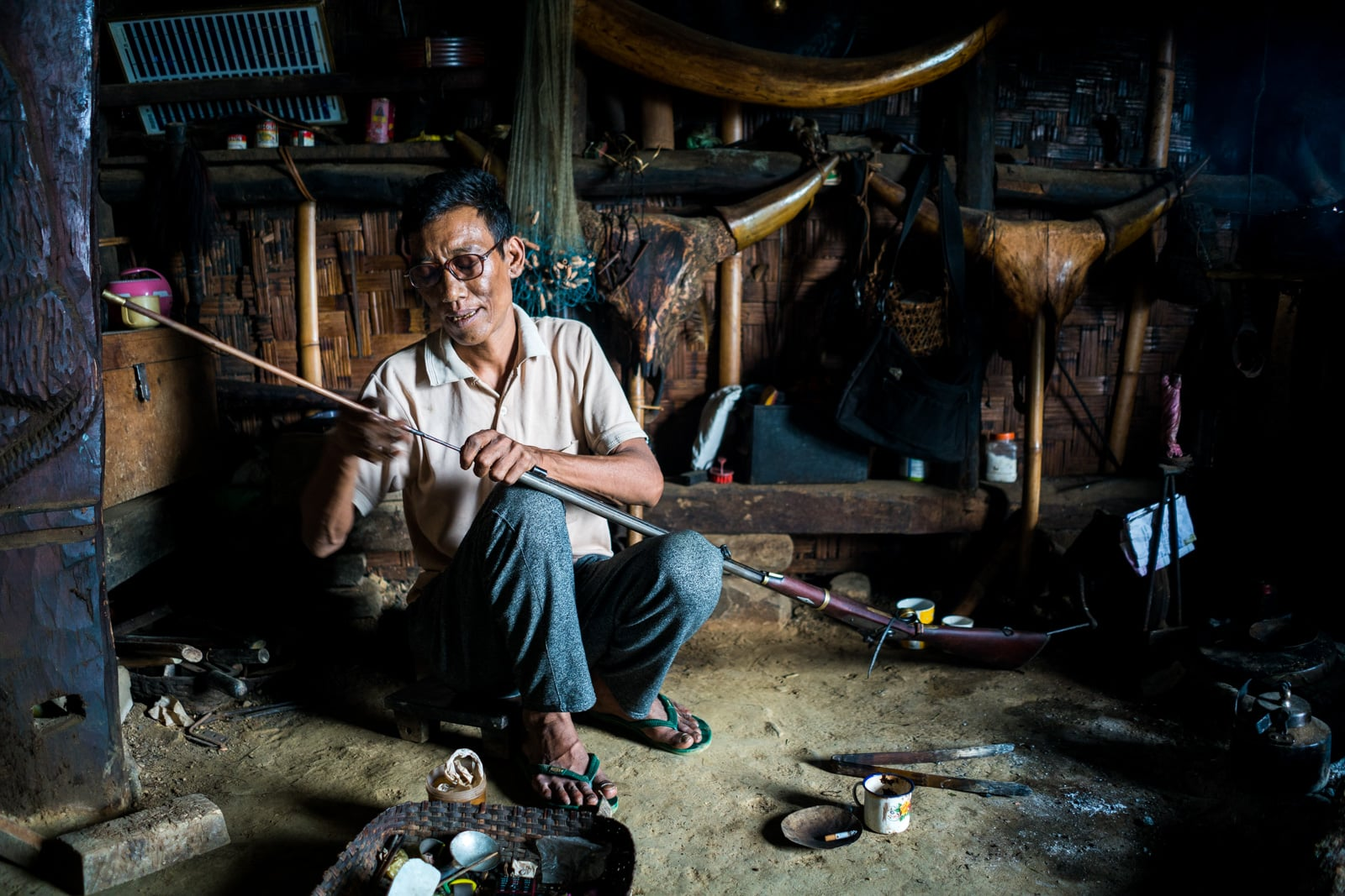 Opium and Jesus and headhunting in Longwa Village, Nagaland, India - Nyakto cleaning a wood paneled rifle - Lost With Purpose