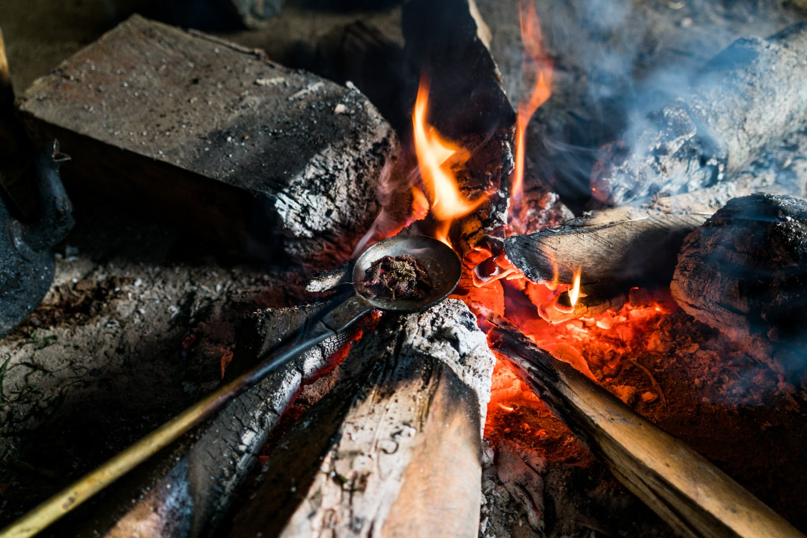 Opium and Jesus and headhunting in Longwa Village, Nagaland, India - Spoon of opium cooking on a fire - Lost With Purpose