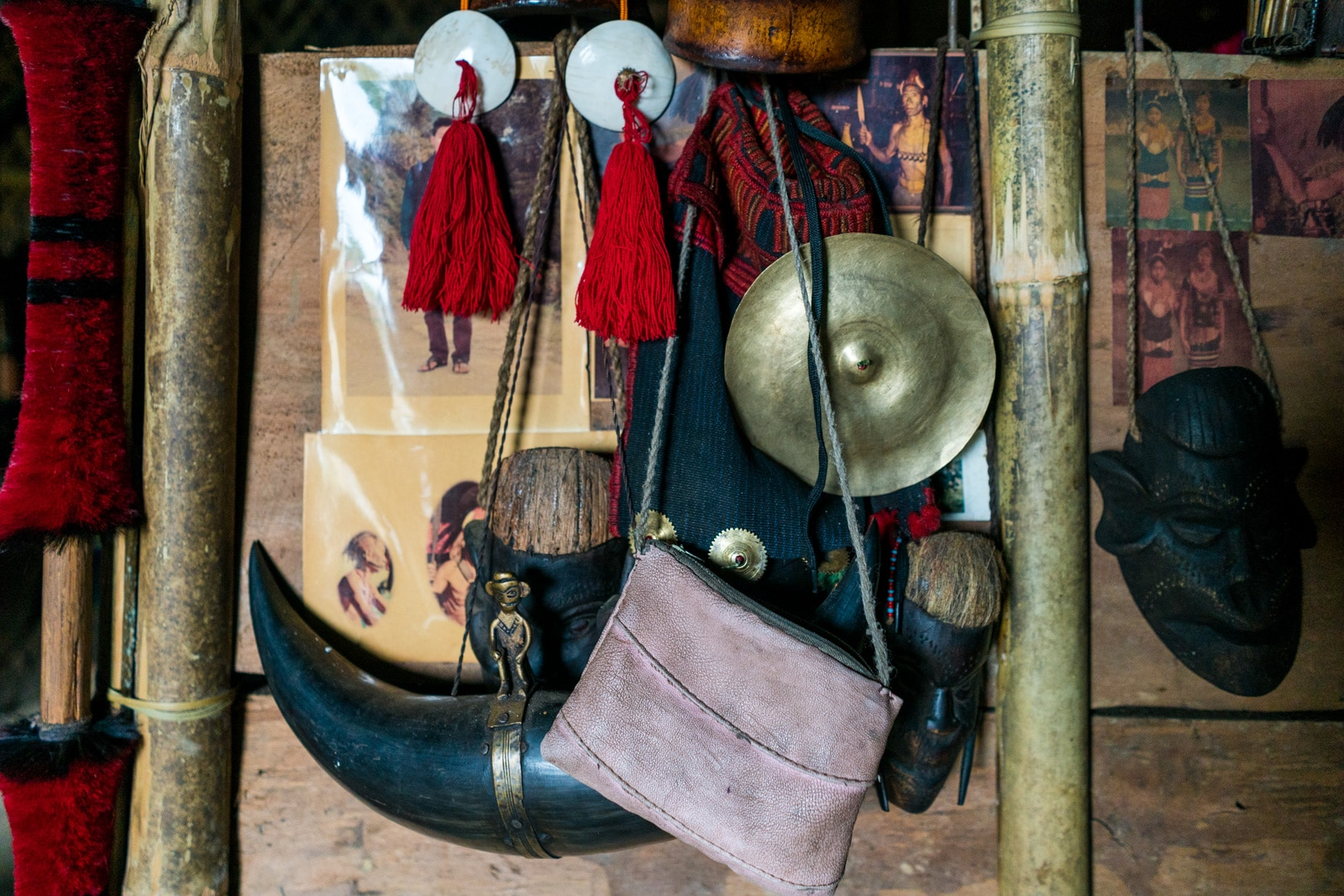 Spears, red tassels, and photos on the bamboo hut wall