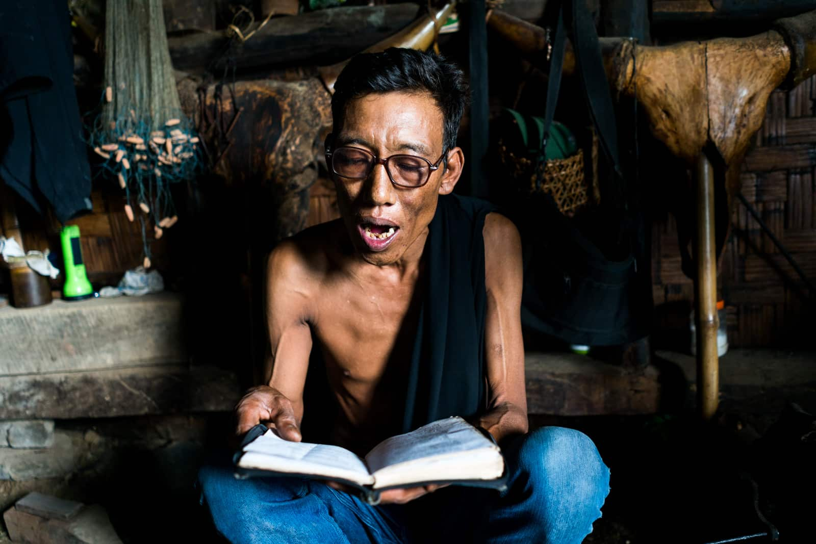Opium and Jesus and headhunting in Longwa Village, Nagaland, India - Homestay host and a Christian church hymn book - Lost With Purpose
