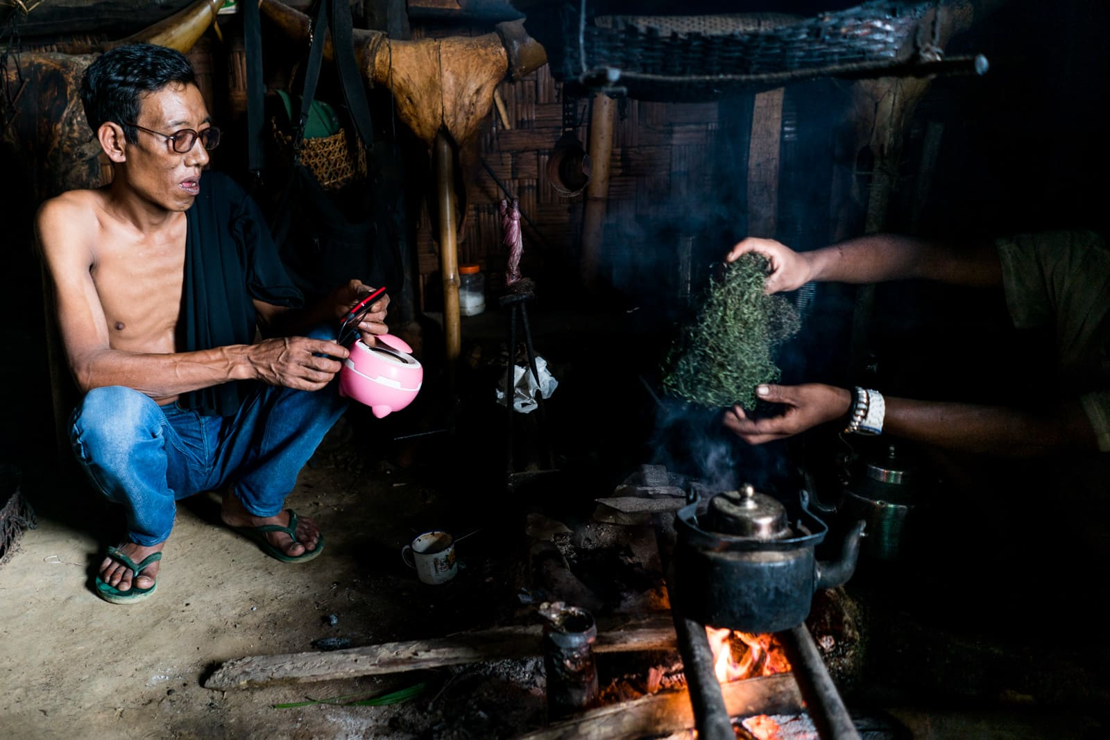 Opium and Jesus and headhunting in Longwa Village, Nagaland, India - Pink portable speakers by the fireside - Lost With Purpose