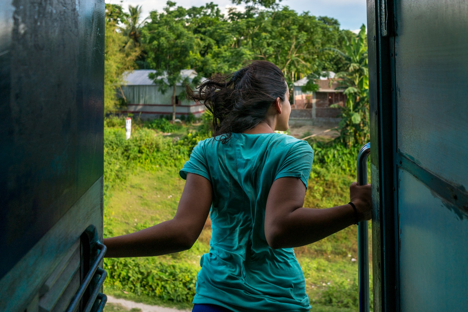 50 ways to deal with excessive sweat while traveling - Alex hanging out of a train in India - Lost With Purpose