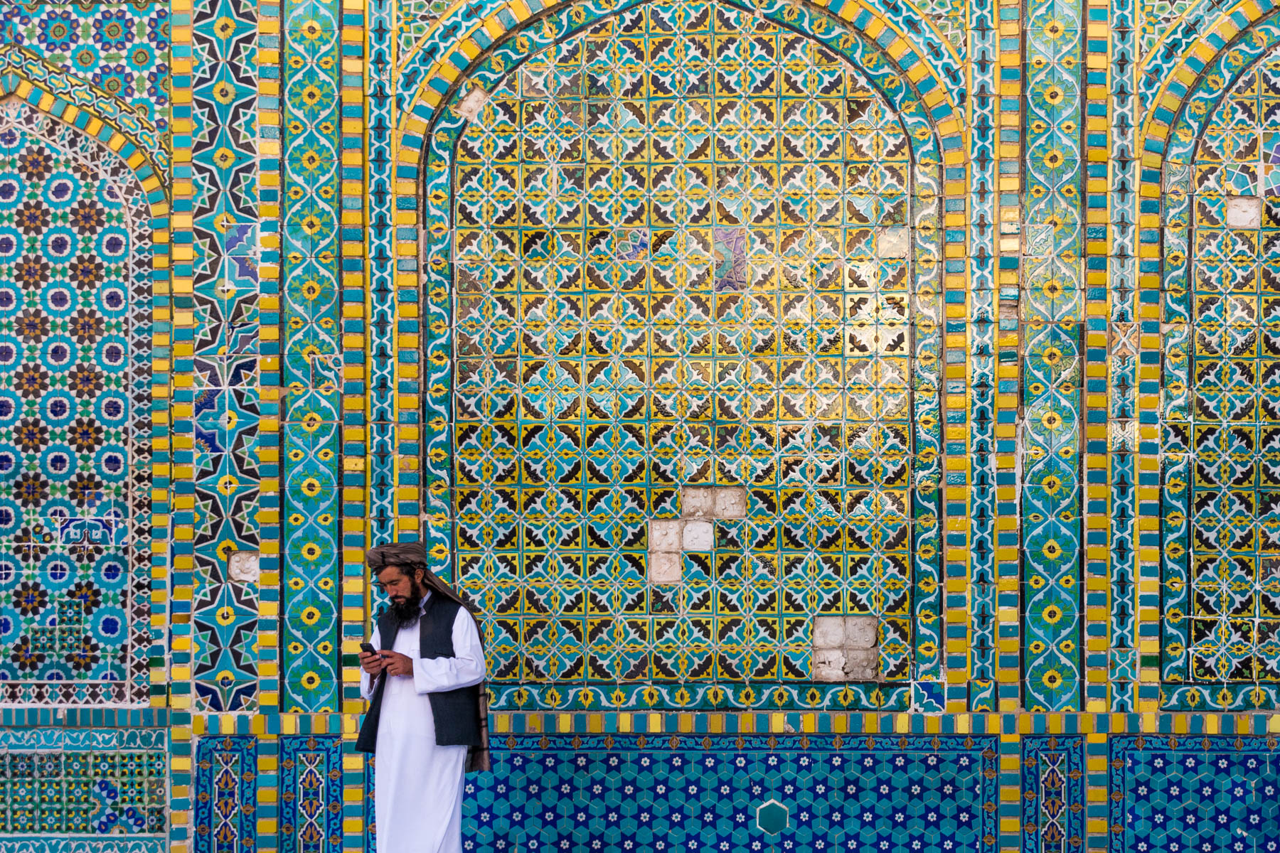 Photos of Mazar-i-Sharif, Afghanistan - Man checking phone in front of the mosaic walls of the Blue Mosque - Lost With Purpose